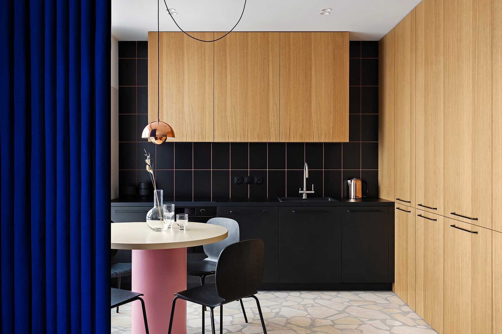 Kitchen with black and pink backsplash separated by blue curtain.