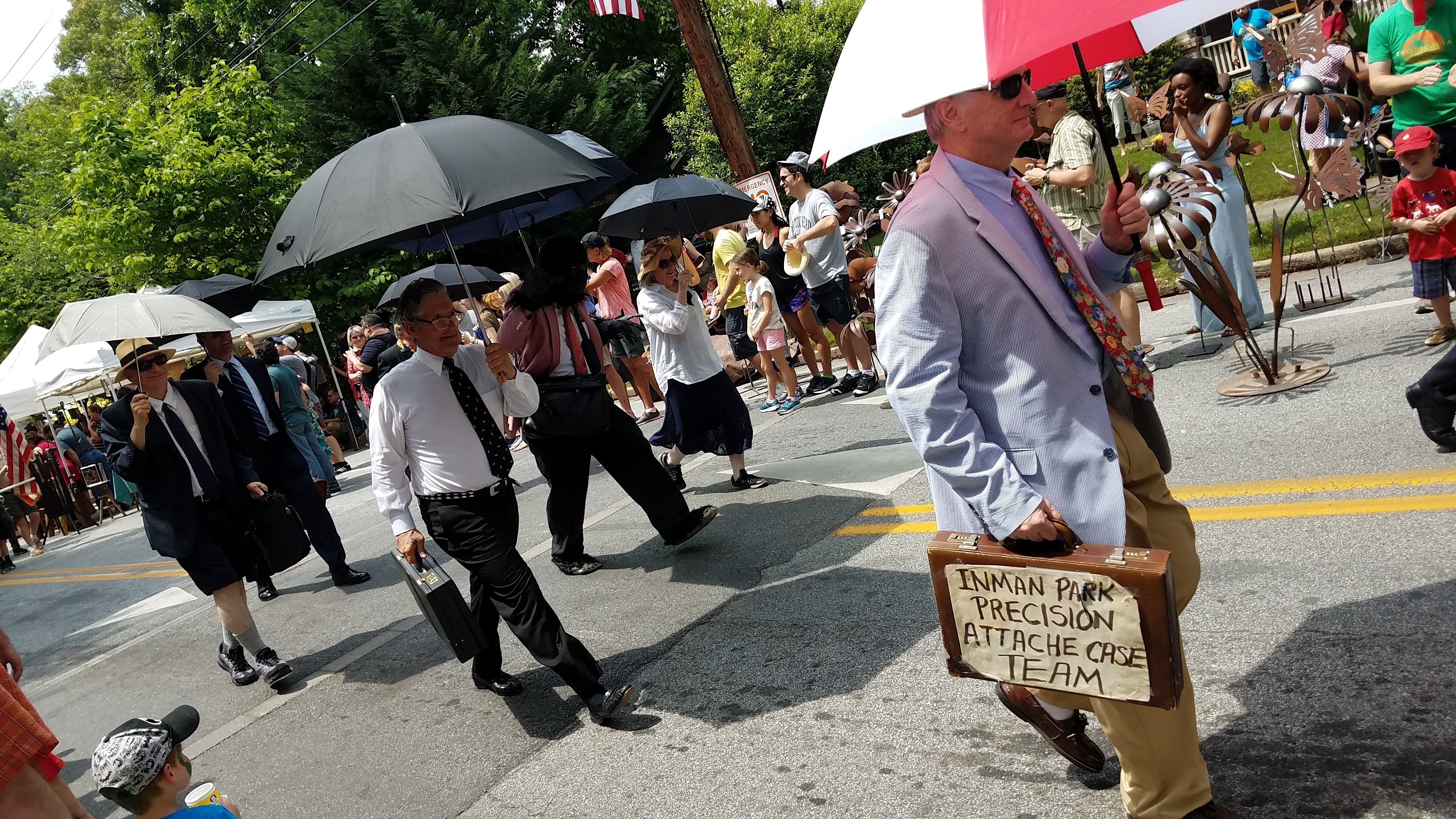 A group of men in a parade use umbrellas over their heads.