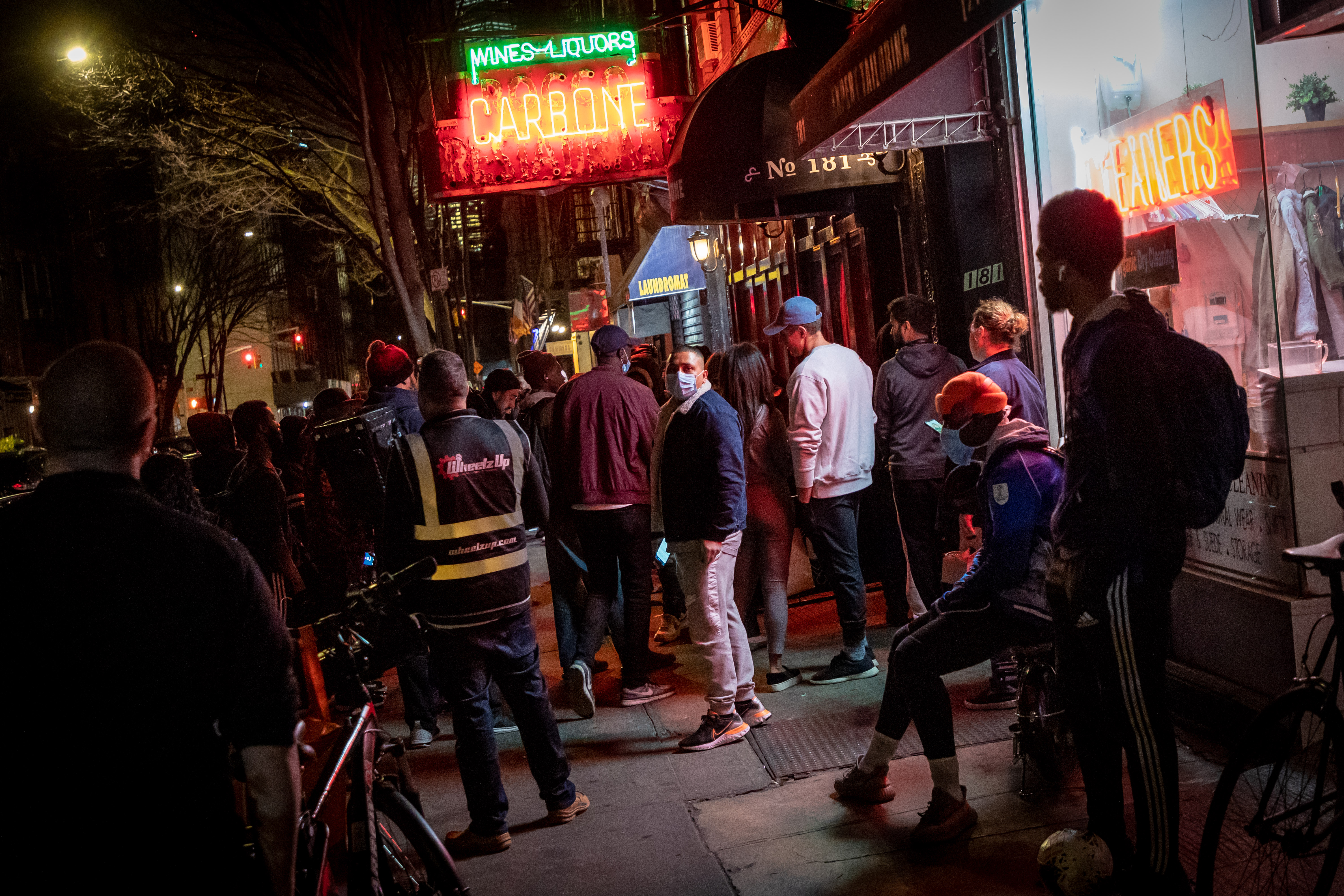 Large crowds of customers and deliverymen mob the outside of Carbone