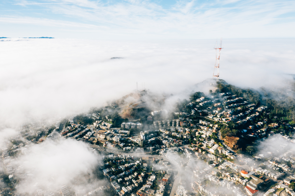 A high aerial photo of homes in the San Francisco hills, with patches of heavy white fog obscuring much of the landscape. A three-pronged broadcast antenna rises hundreds of feet into the air from a hilltop.