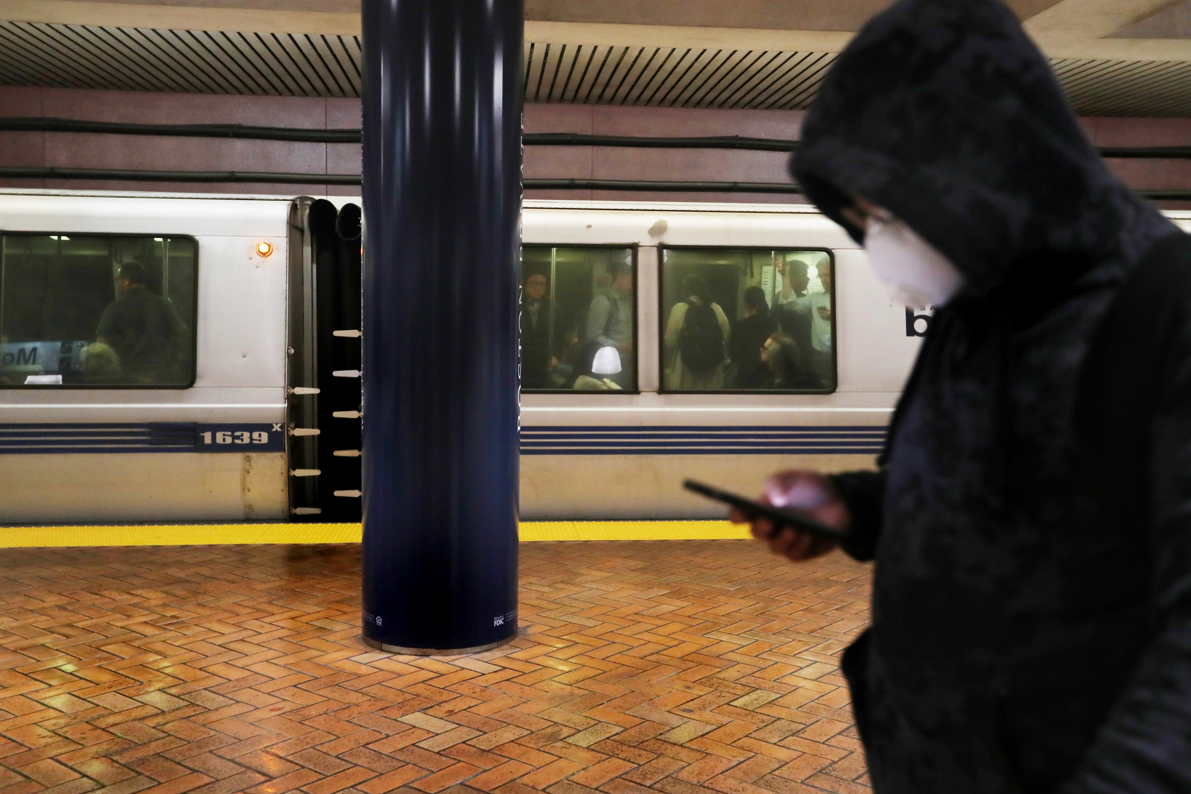 A man wearing a dark hoodie and a white mask over his nose and mouth, while standing on a train platform with a blue and gray train behind him.