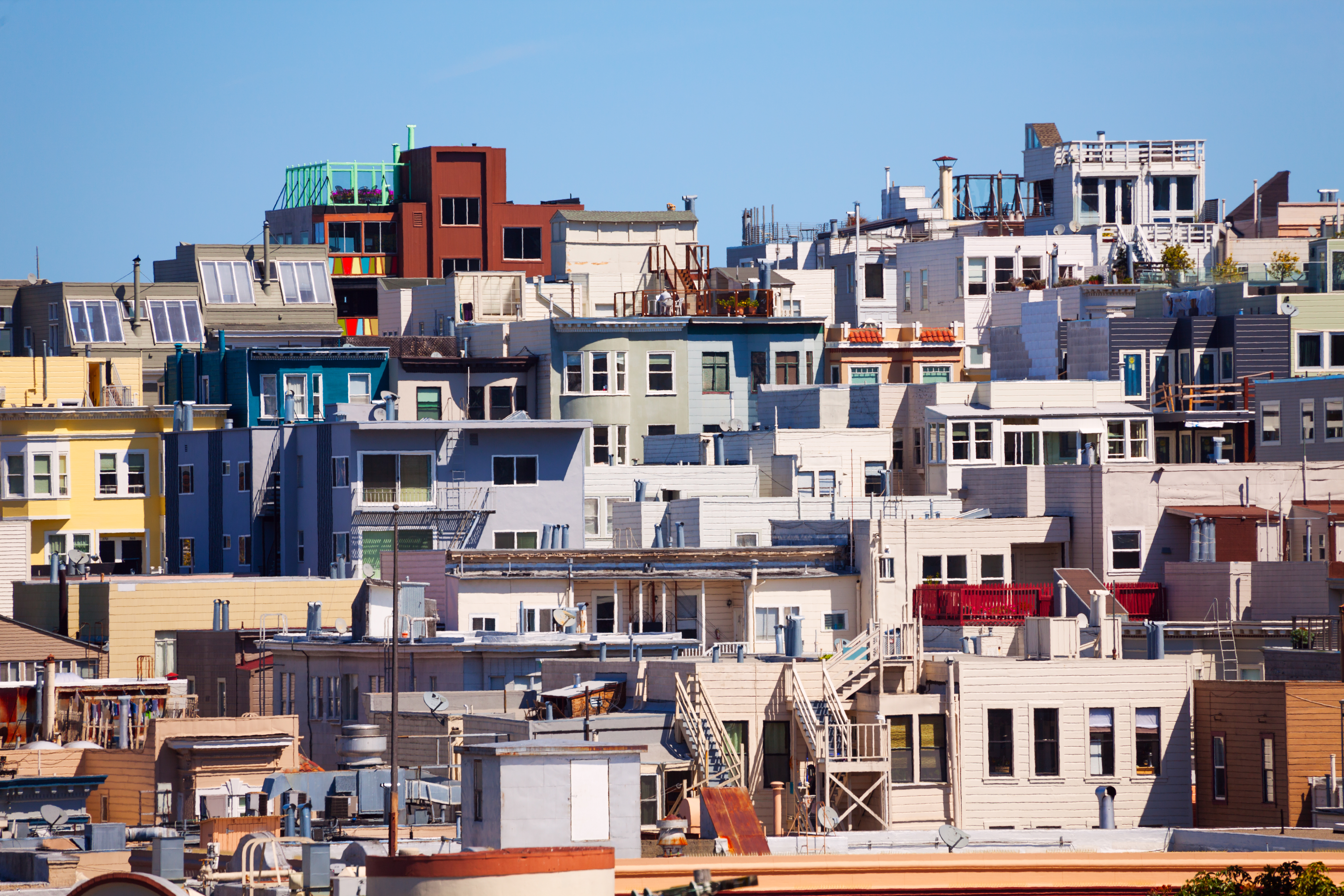 A series of colorful mid-rise apartment buildings from the 1920s through the 1940s, all clustered together on a hillside under a blue sky.
