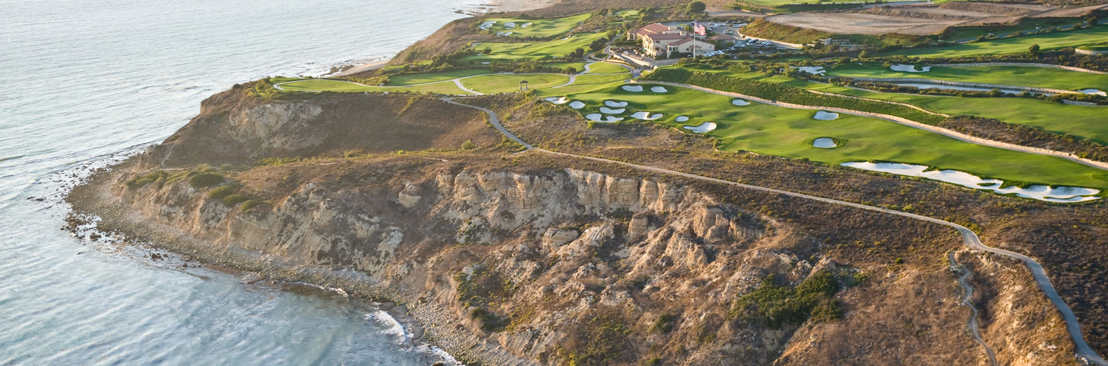 A rocky shoreline and, above, a manicured golf course and club area.