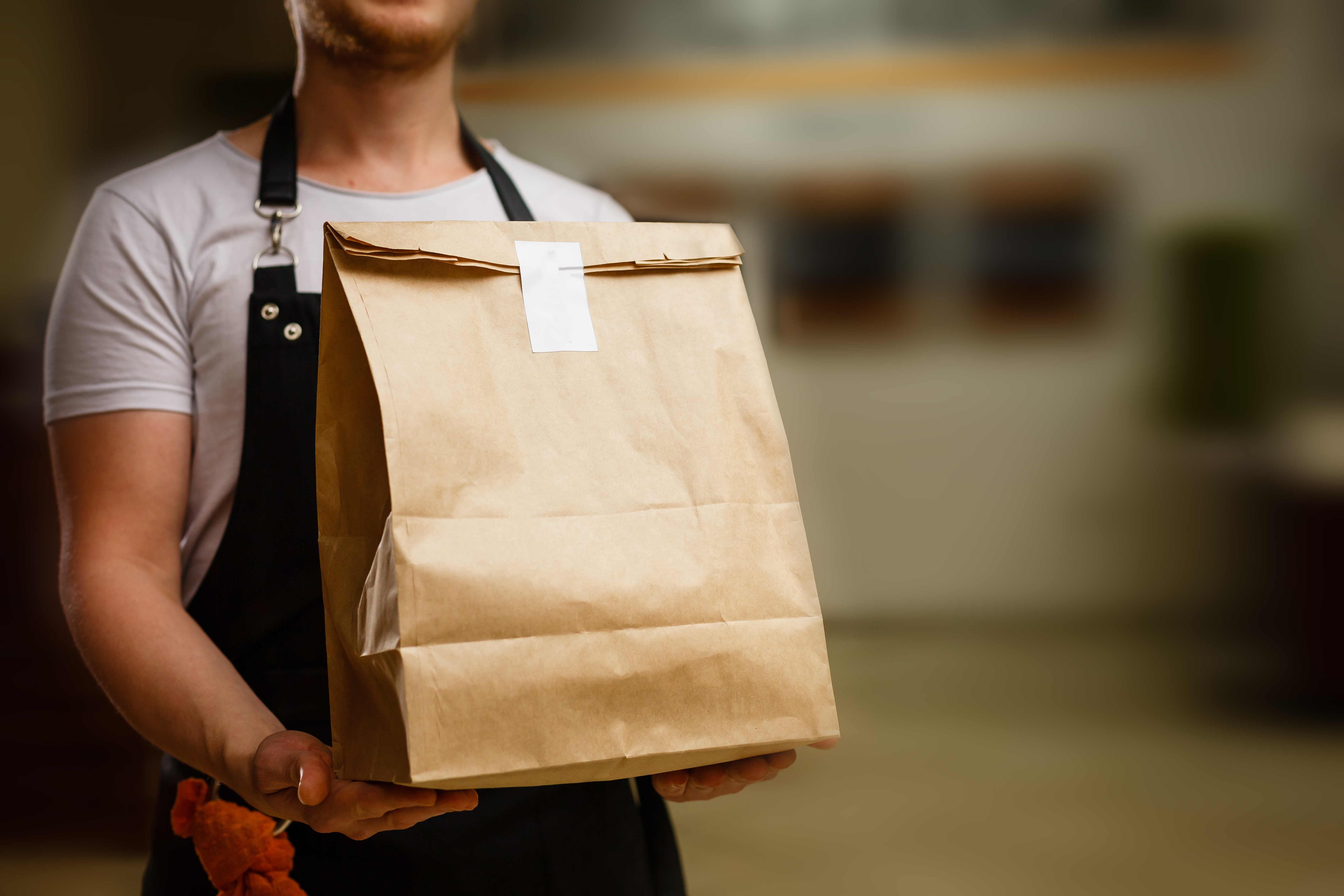 Stock photograph of a man in an apron holding a brown paper bag, ostensibly full of food for delivery