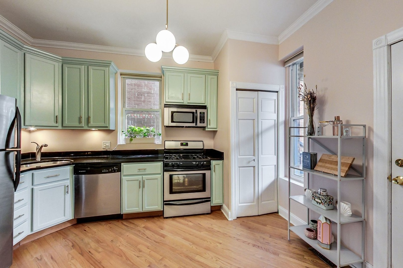 A kitchen with mint cabinets, open shelving and a large window.