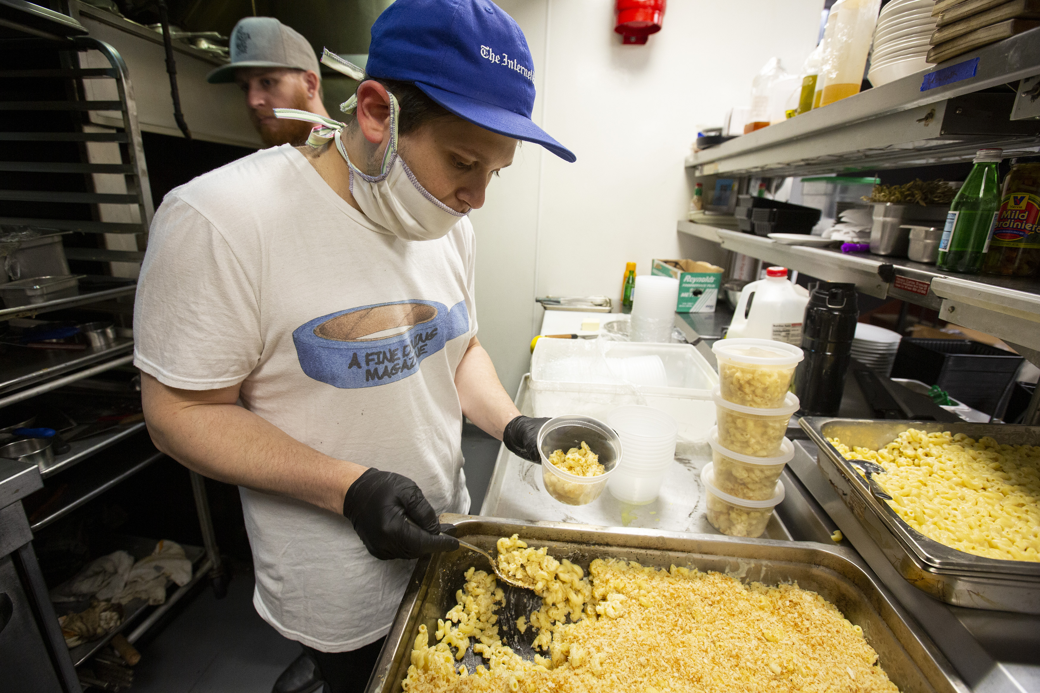 A man wearing a medical mask scoops mac and cheese into plastic containers.