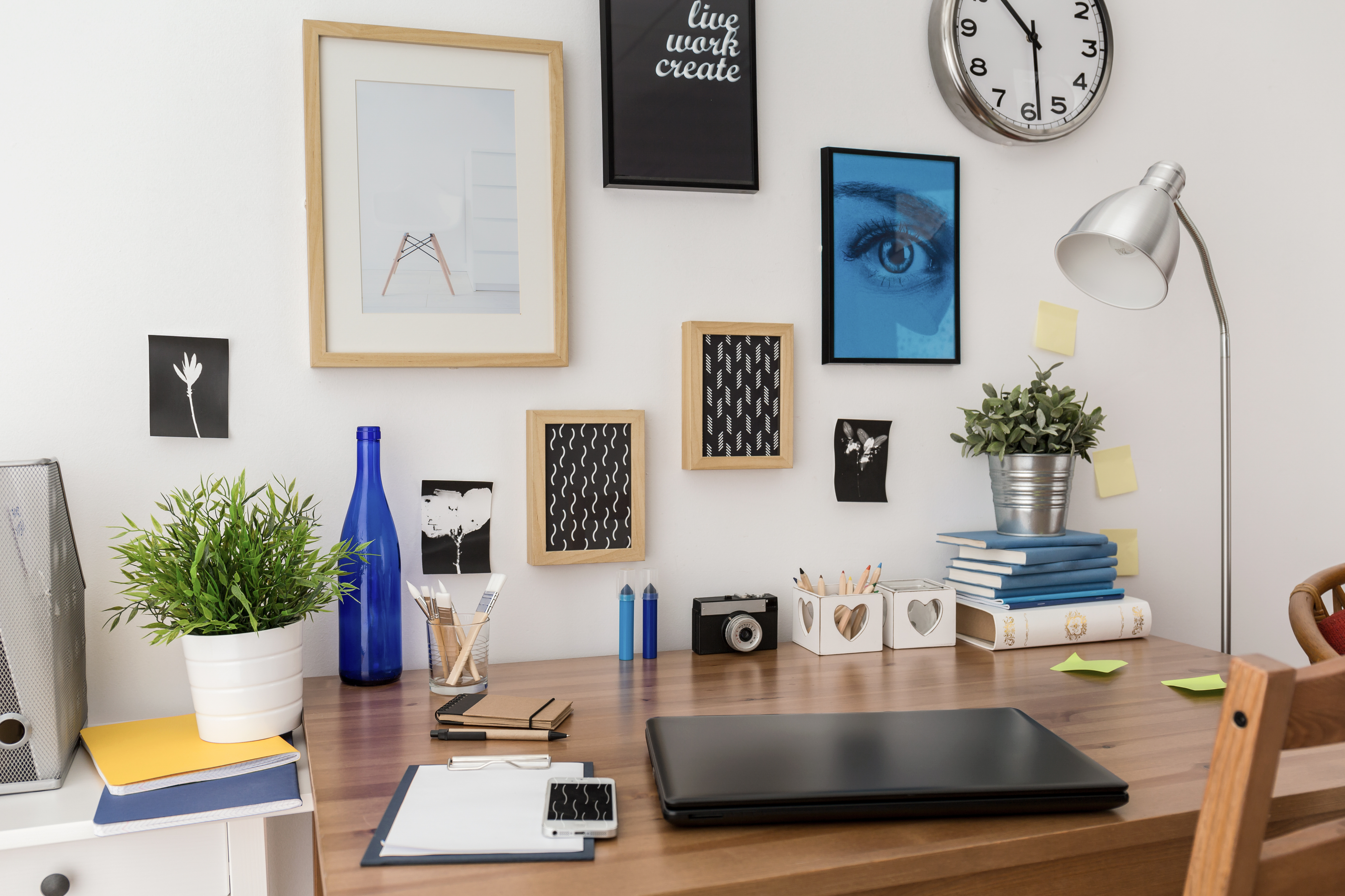 A well-organized desk against a wall, with a closed laptop, a potted plant, and a lamp, and there's a clock on the wall.