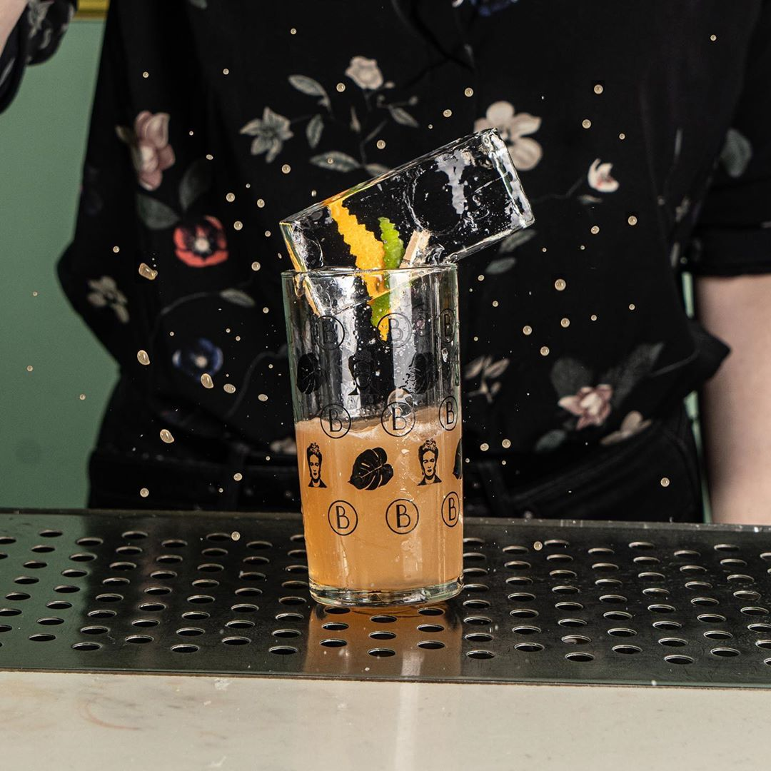 A pink cocktail half fills a highball glass that has a black printed pattern on it that includes Frida Kahlo's face. The glass is garnished with a giant ice cube.