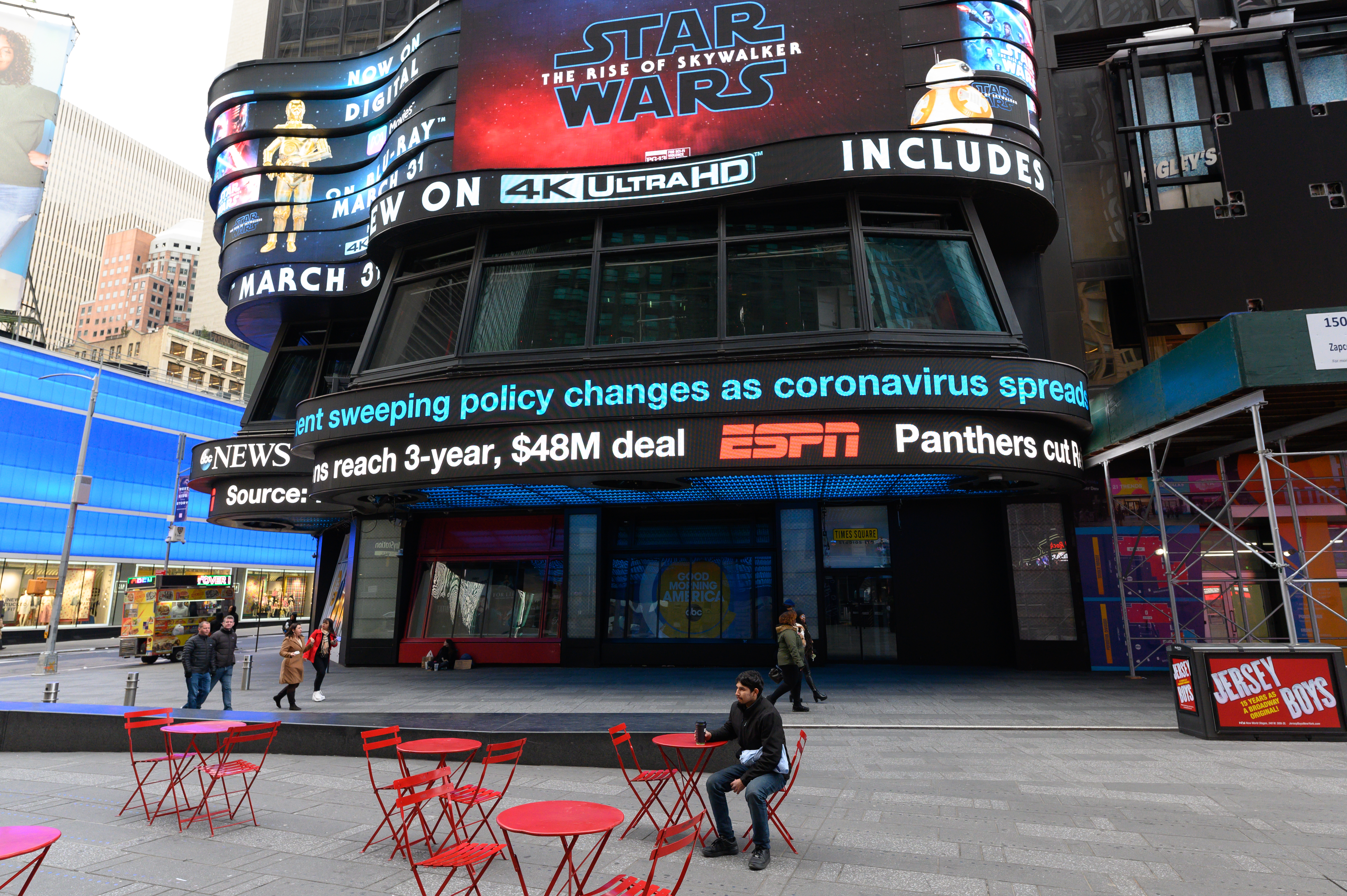 A man sits alone in a chair in front of some Times Square billboards on March 18, 2020.