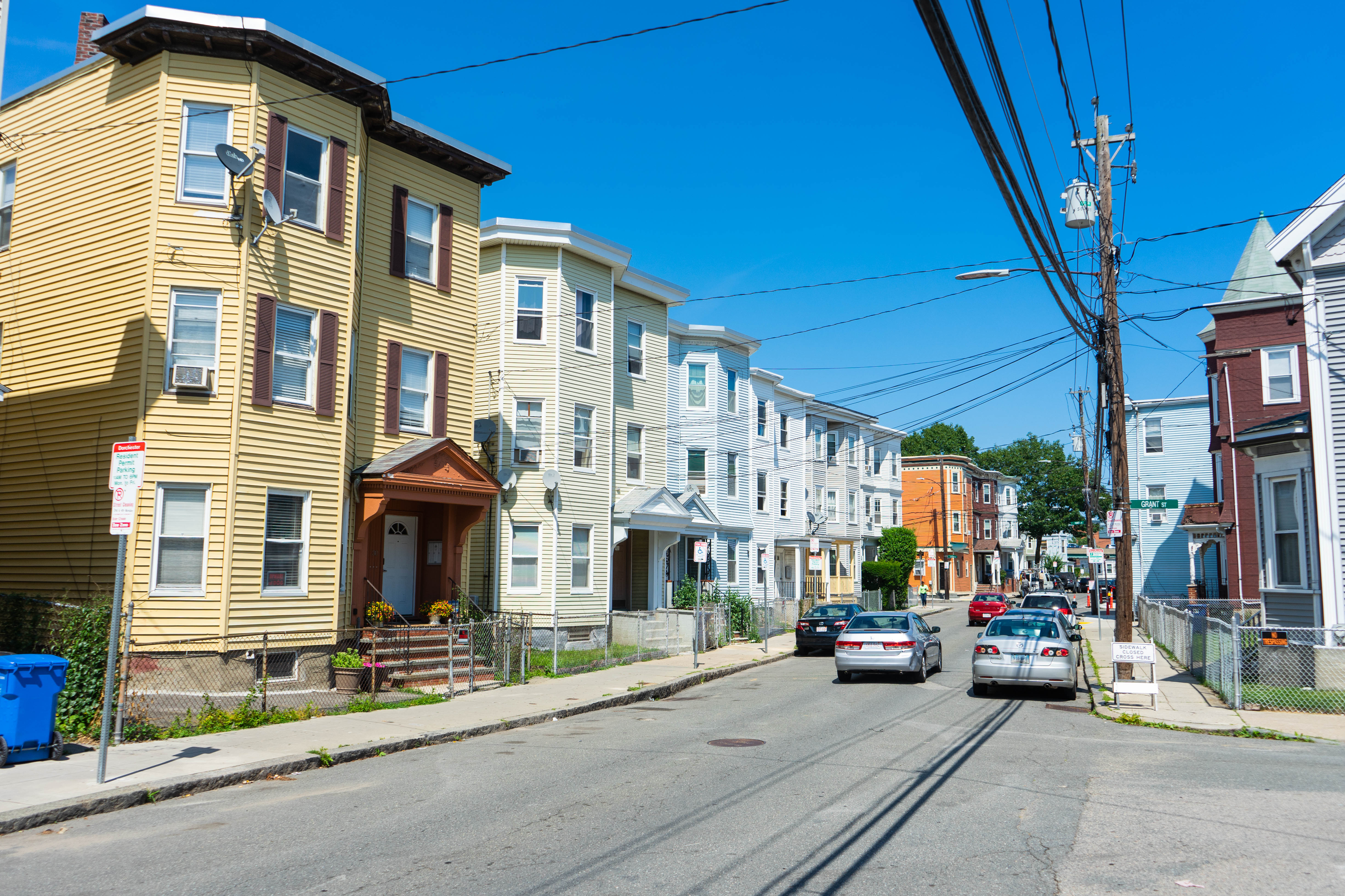 A row of three-story residential buildings along a city street, with cars parked along the street.