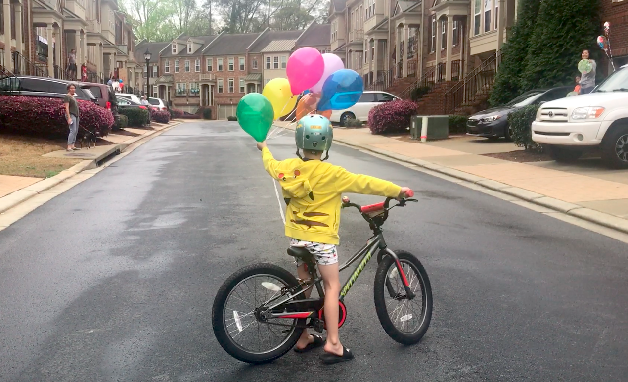 A little boy has a lot of balloons tied to his bike in a community of townhomes.