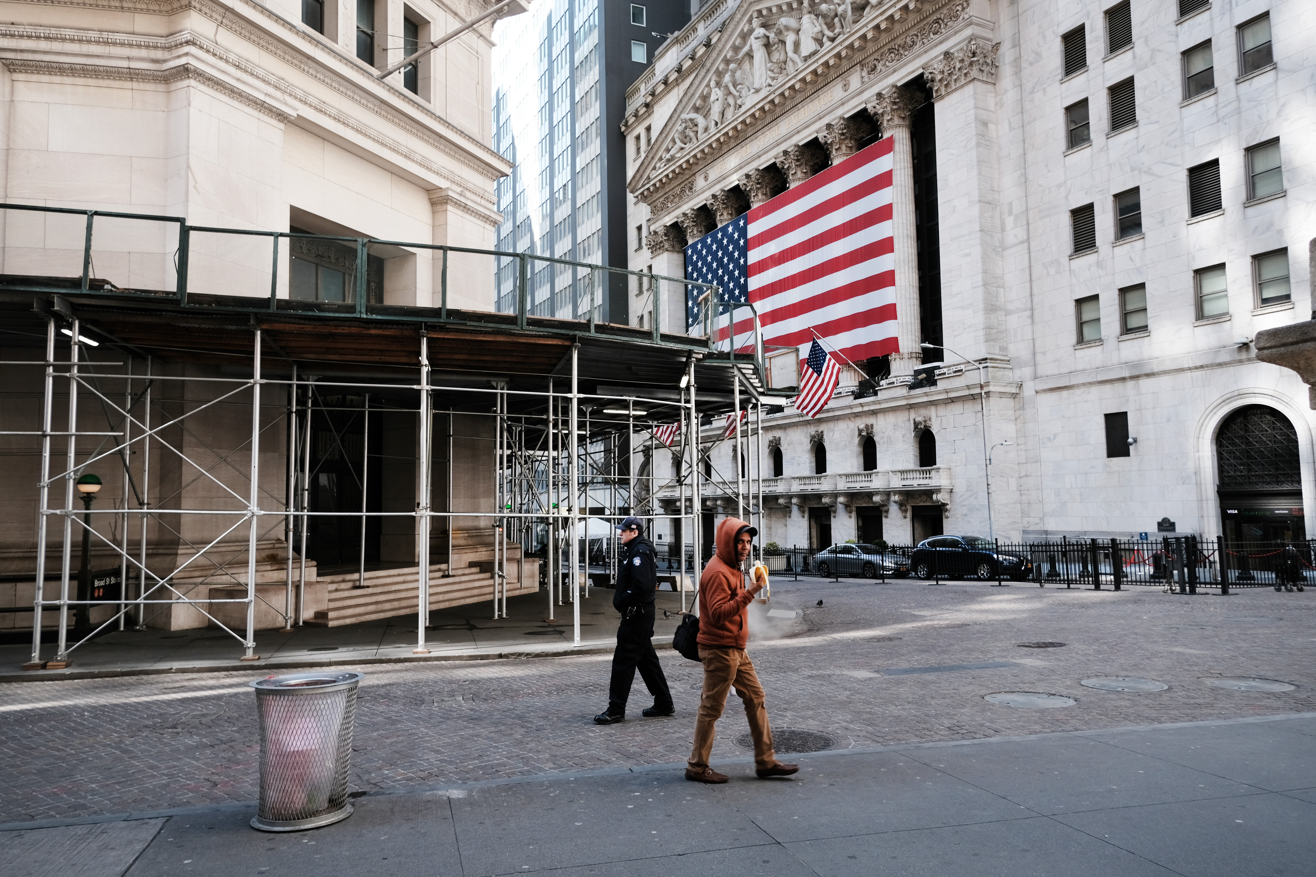 Two men walk in front of the New York Stock Exchange on March 24, 2020.