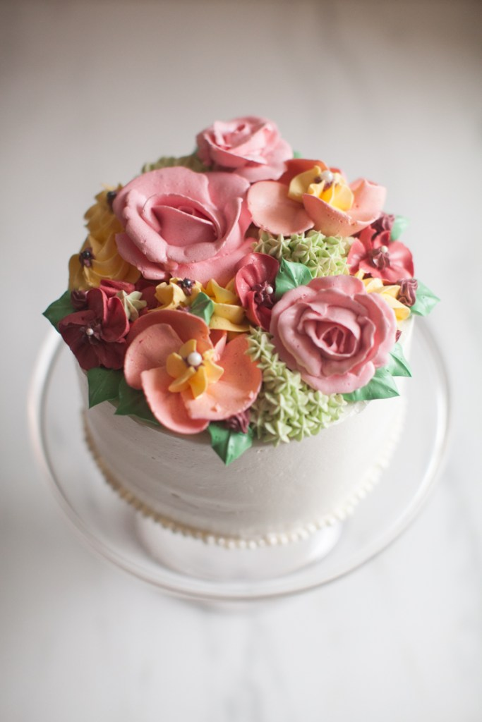 A white buttercream cake topped with pastel roses