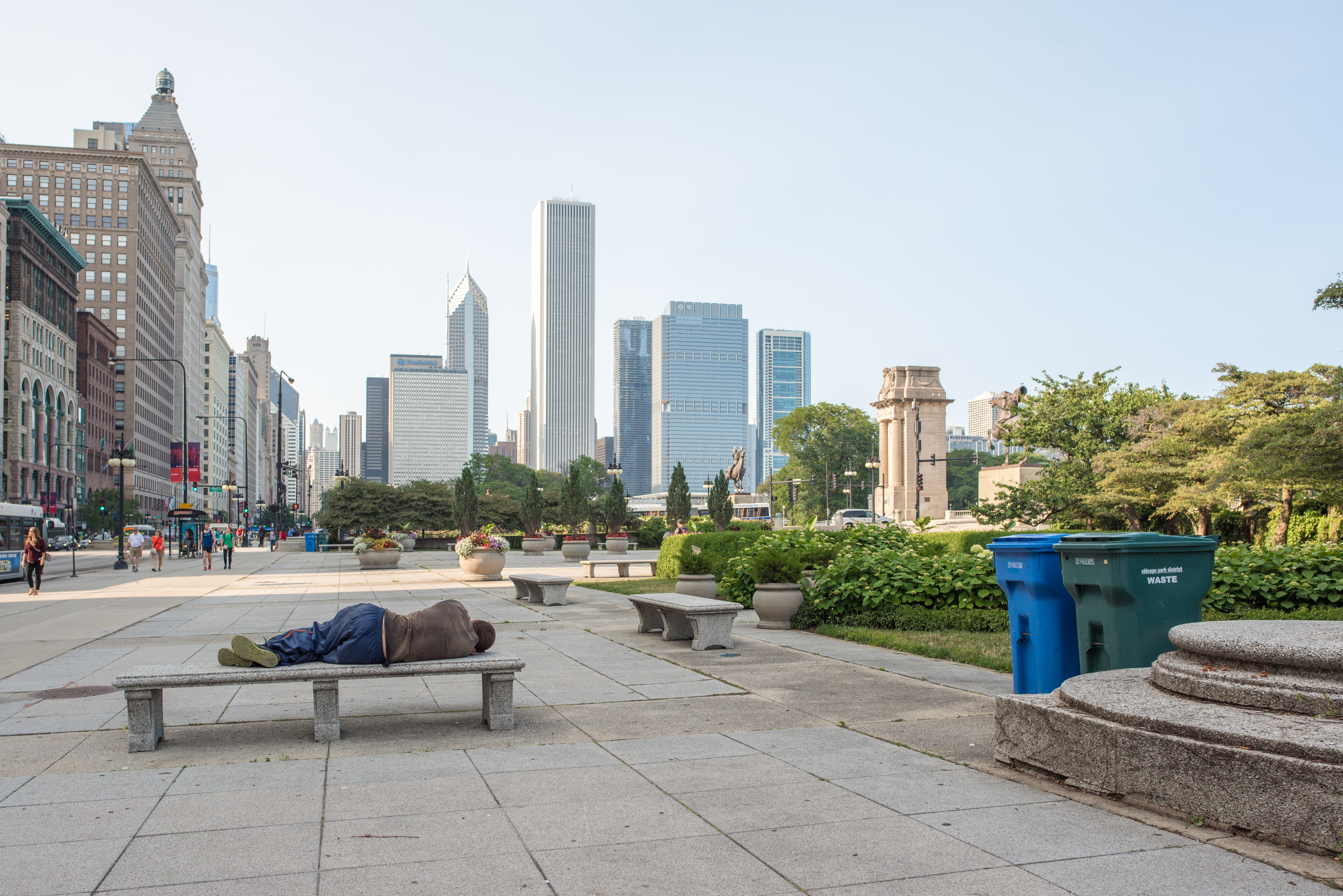 A bench in a Chicago park with buildings in the background.