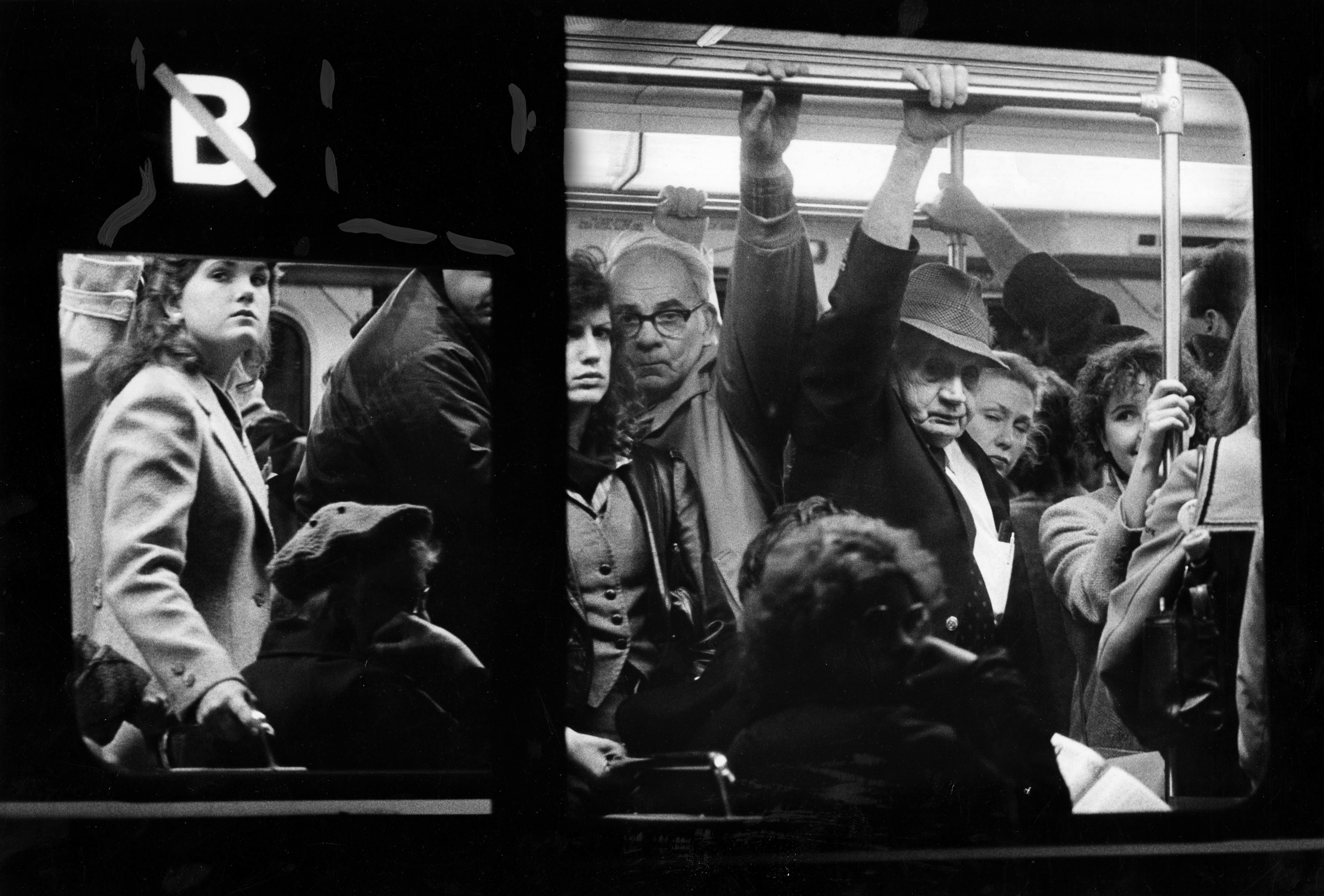 A crowded subway train as seen through one of its windows.