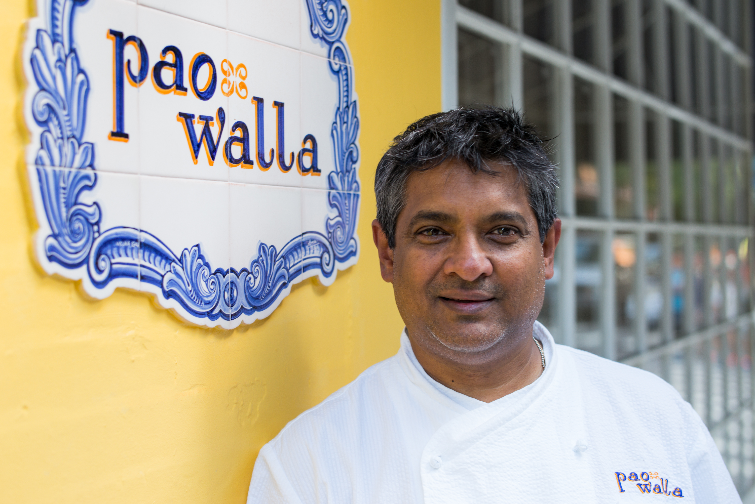 Floyd Cardoz in front of Paowalla's yellow wall