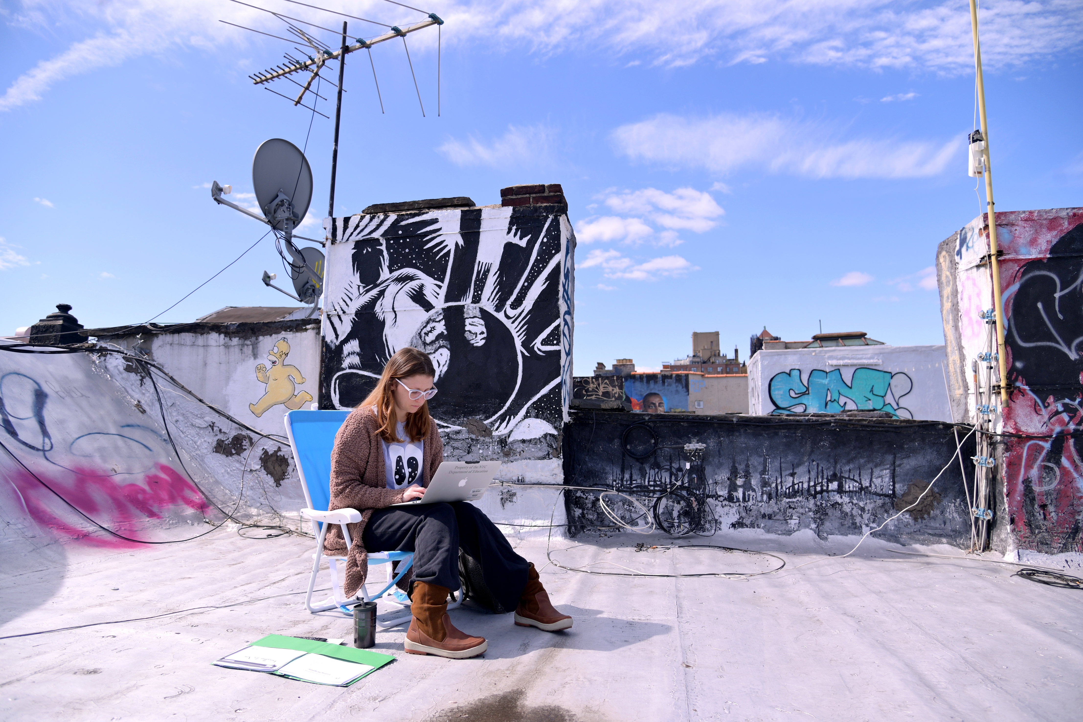 A woman uses a laptop on a roof in New York City.