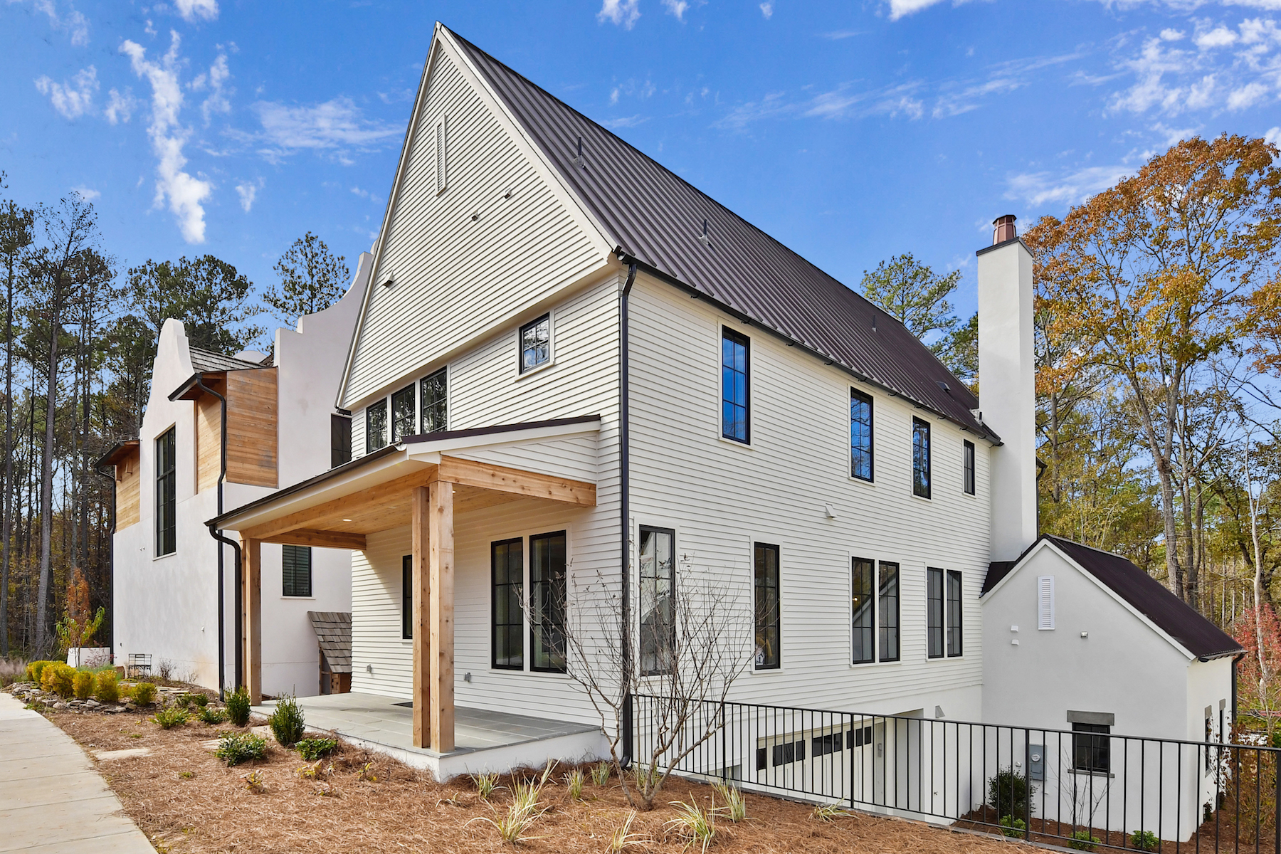 White three-story farmhouse-style home with small covered front porch.