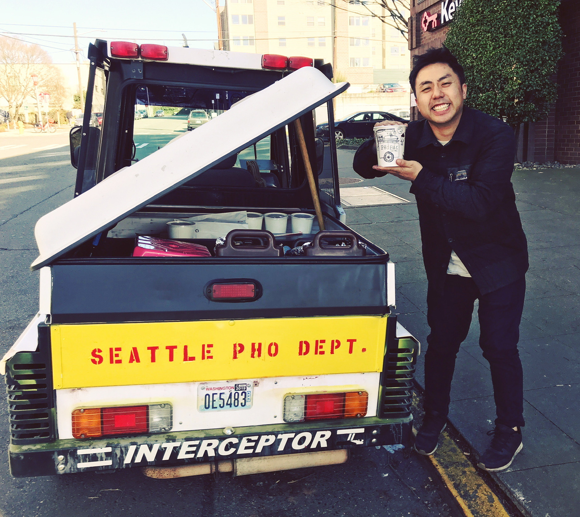 """Khoa Pham poses in front of a parking enforcement vehicle that says """"Seattle Pho Dept"""" on the back in red paint."""