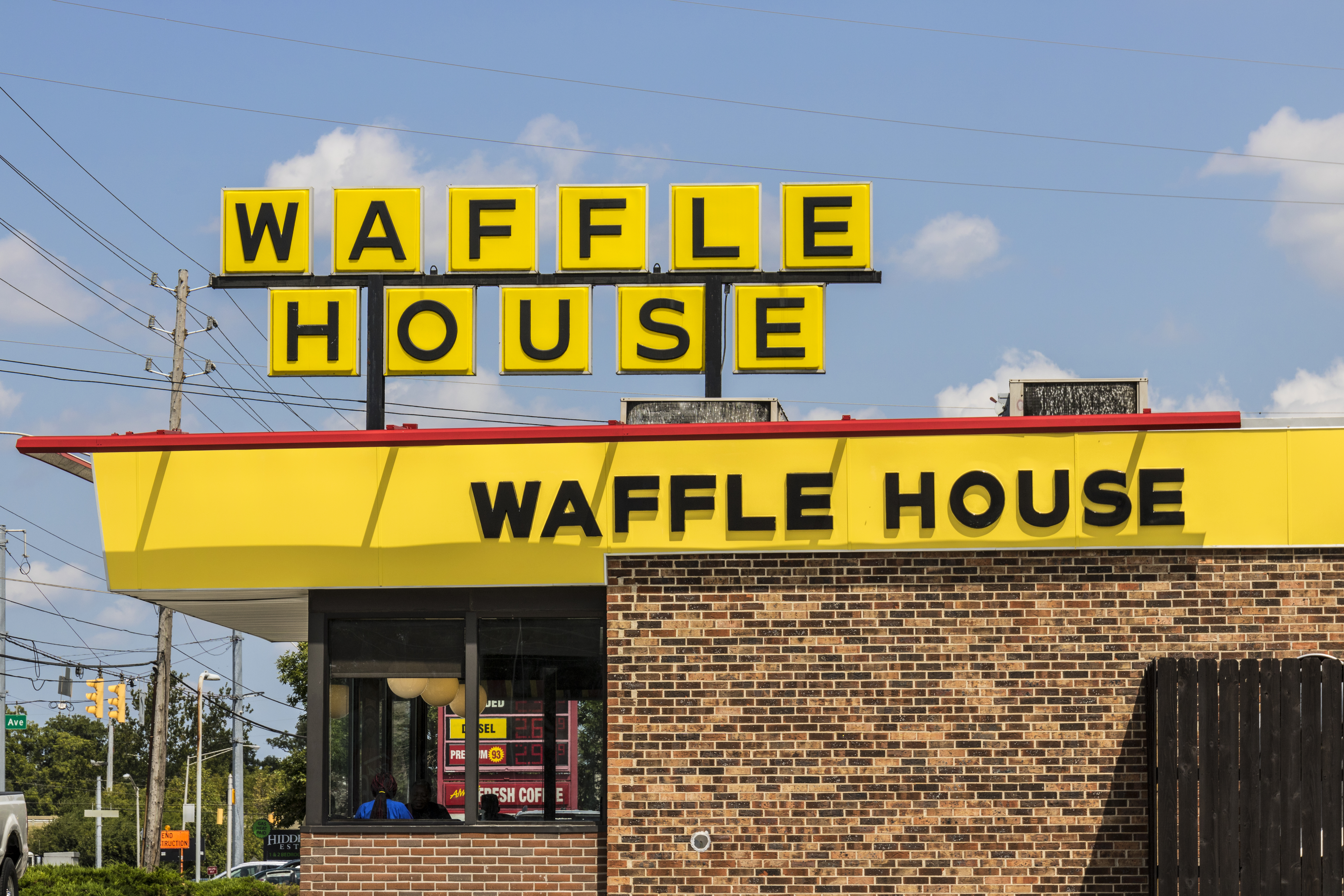 Exterior of a Waffle House restaurant, with a Waffle House sign in the background.