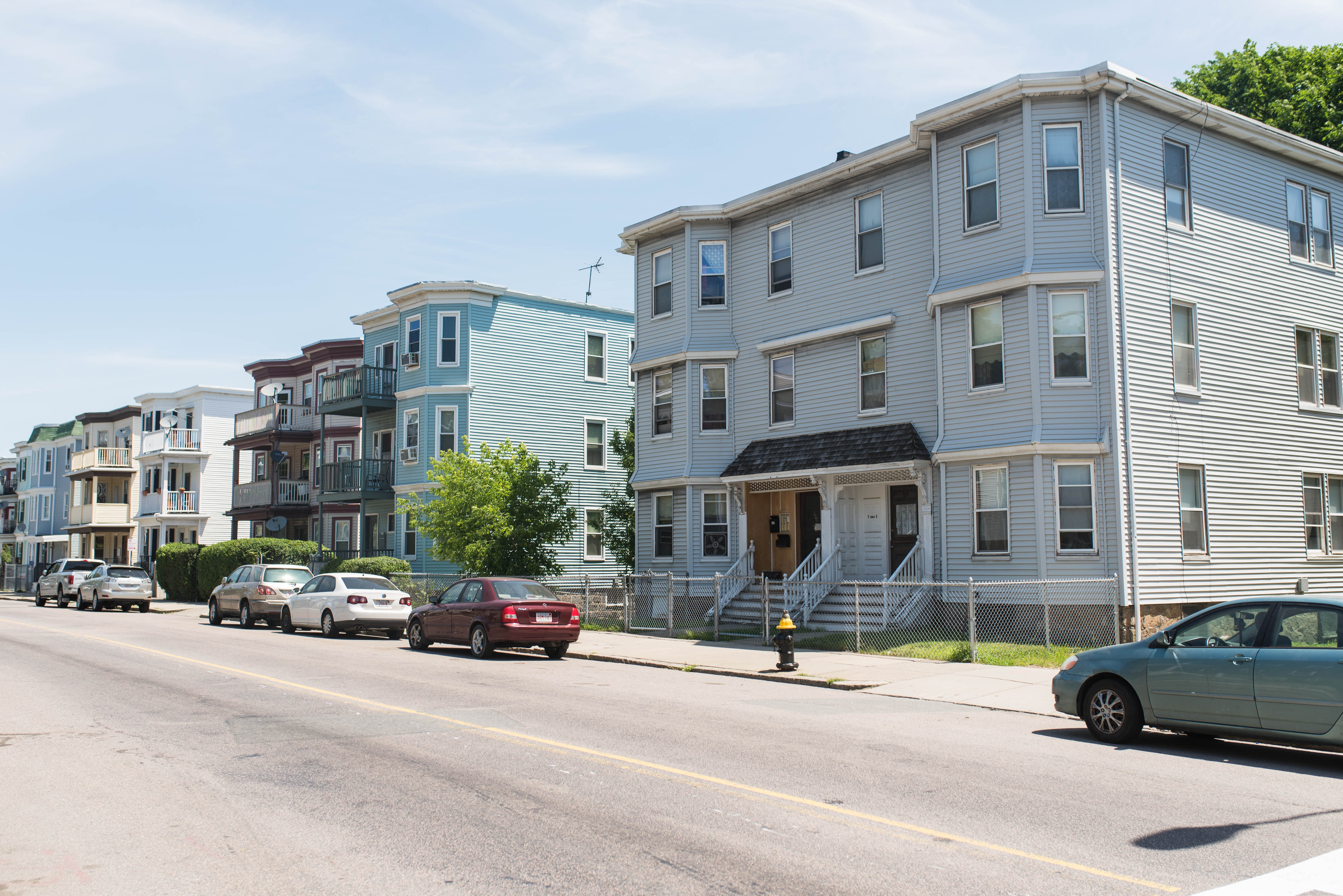 The long view of a row of three-story apartment buildings.