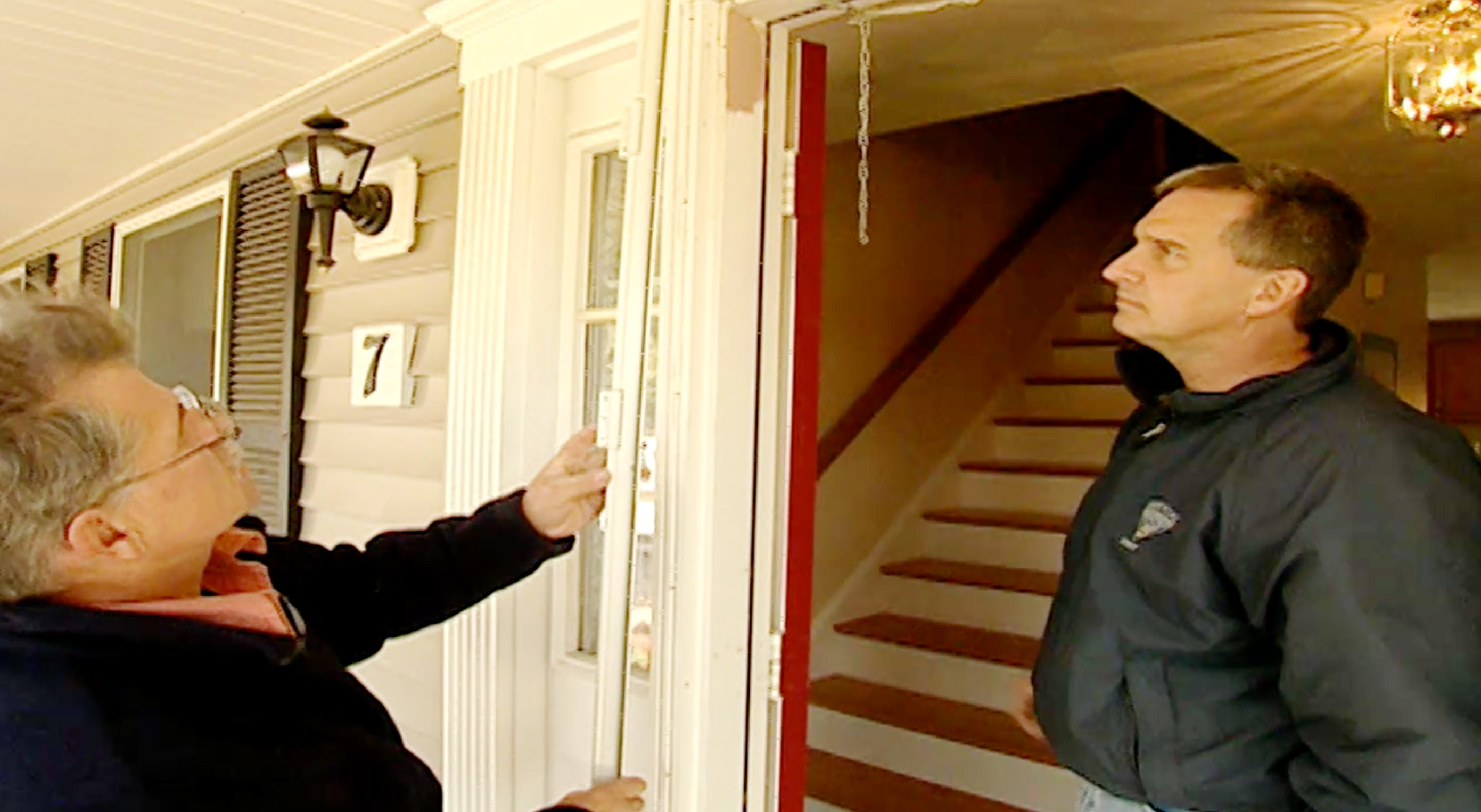 Two people inspect a frosted screen door.