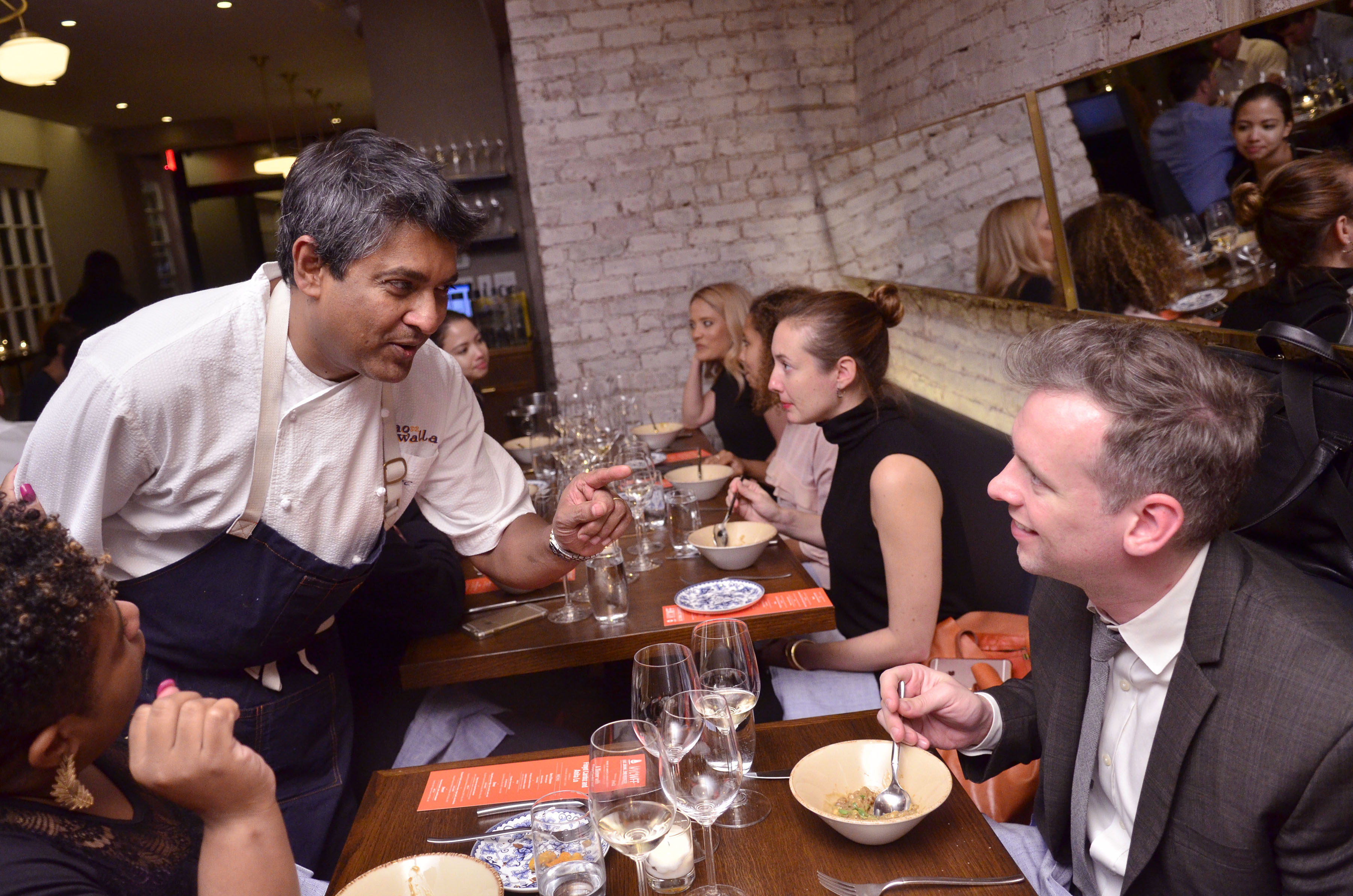 Floyd Cardoz talks to a guest seated at a restaurant table.