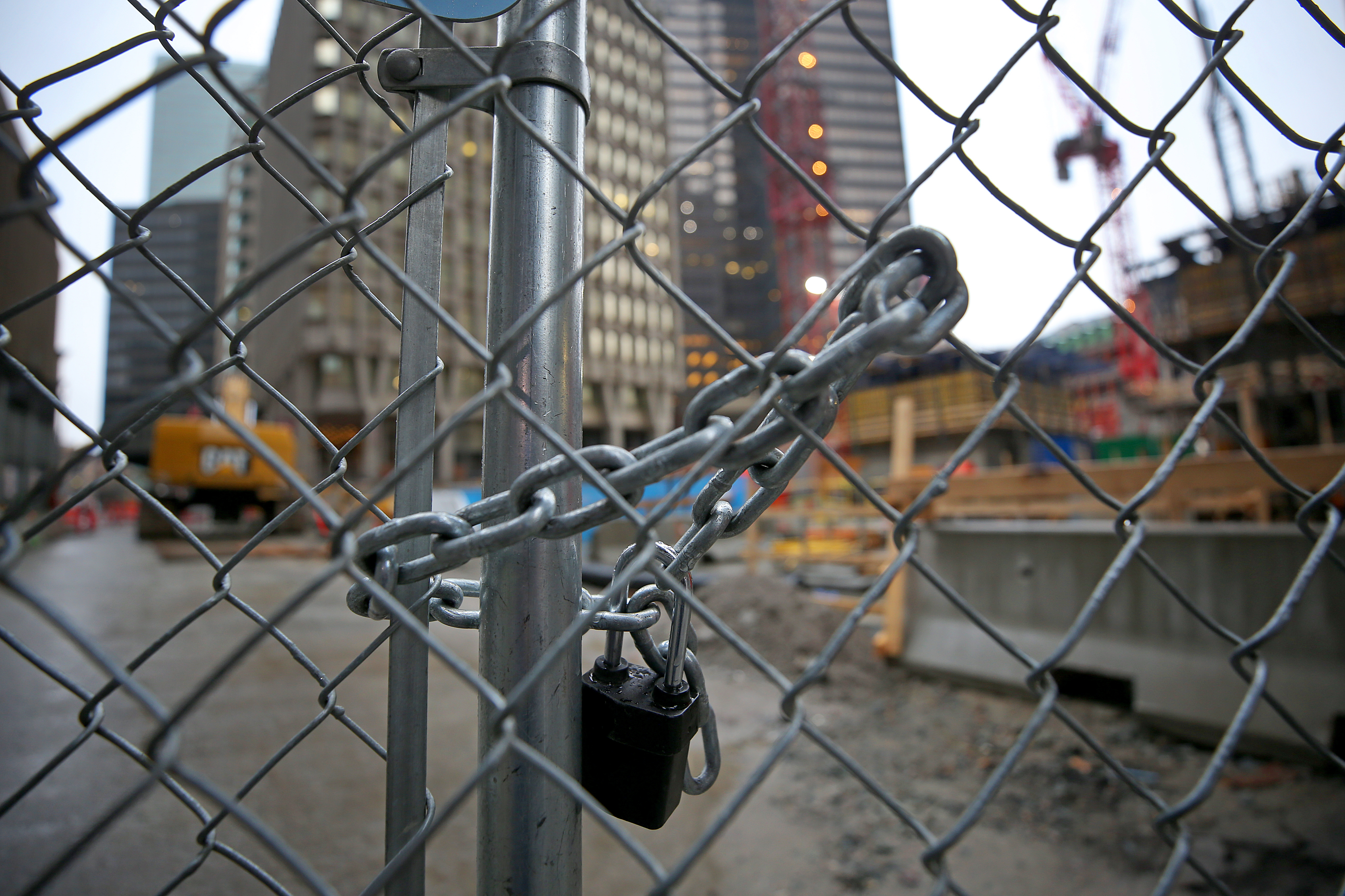 A locked chain around a chain-linked fence surrounding a construction site.