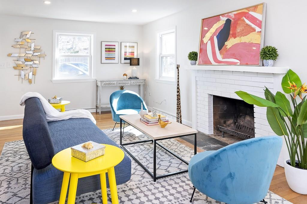 Bright living room with three chairs arranged around a fireplace.