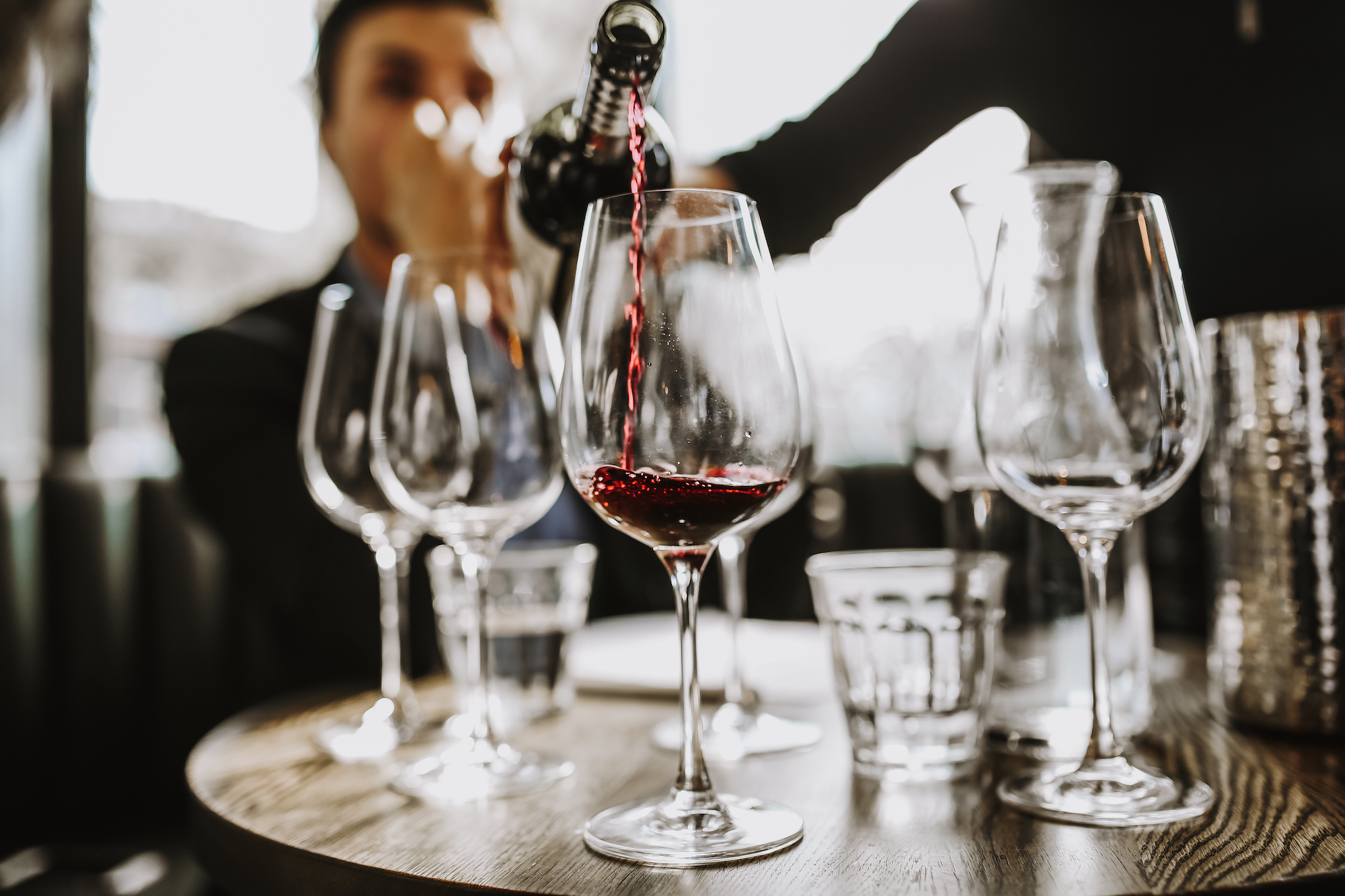 A sommelier mostly out of frame pours a glass of red wine for a customer