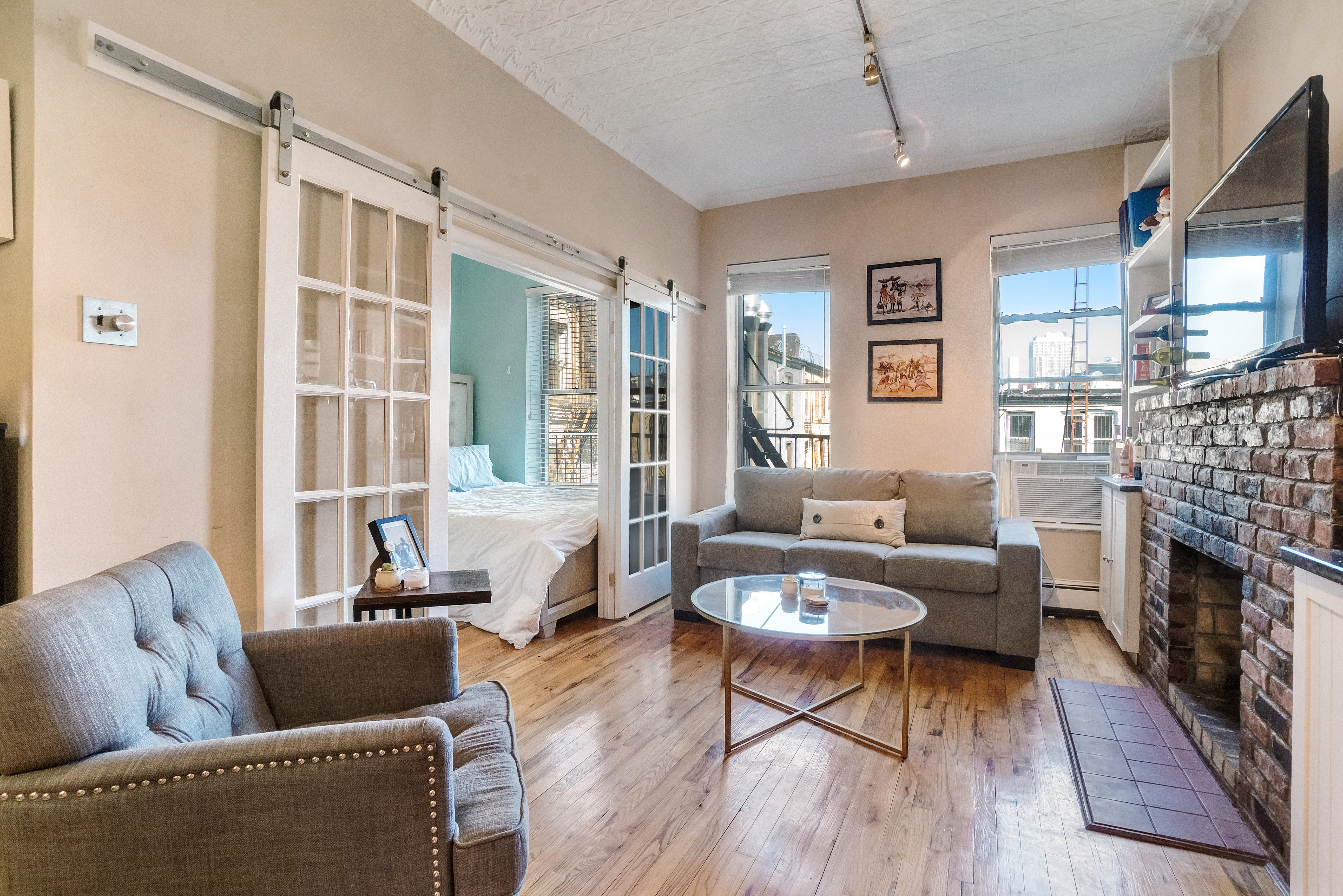A living area with hardwood floors, two windows, a glass coffee table, exposed brick, and a wood-burning fireplace.