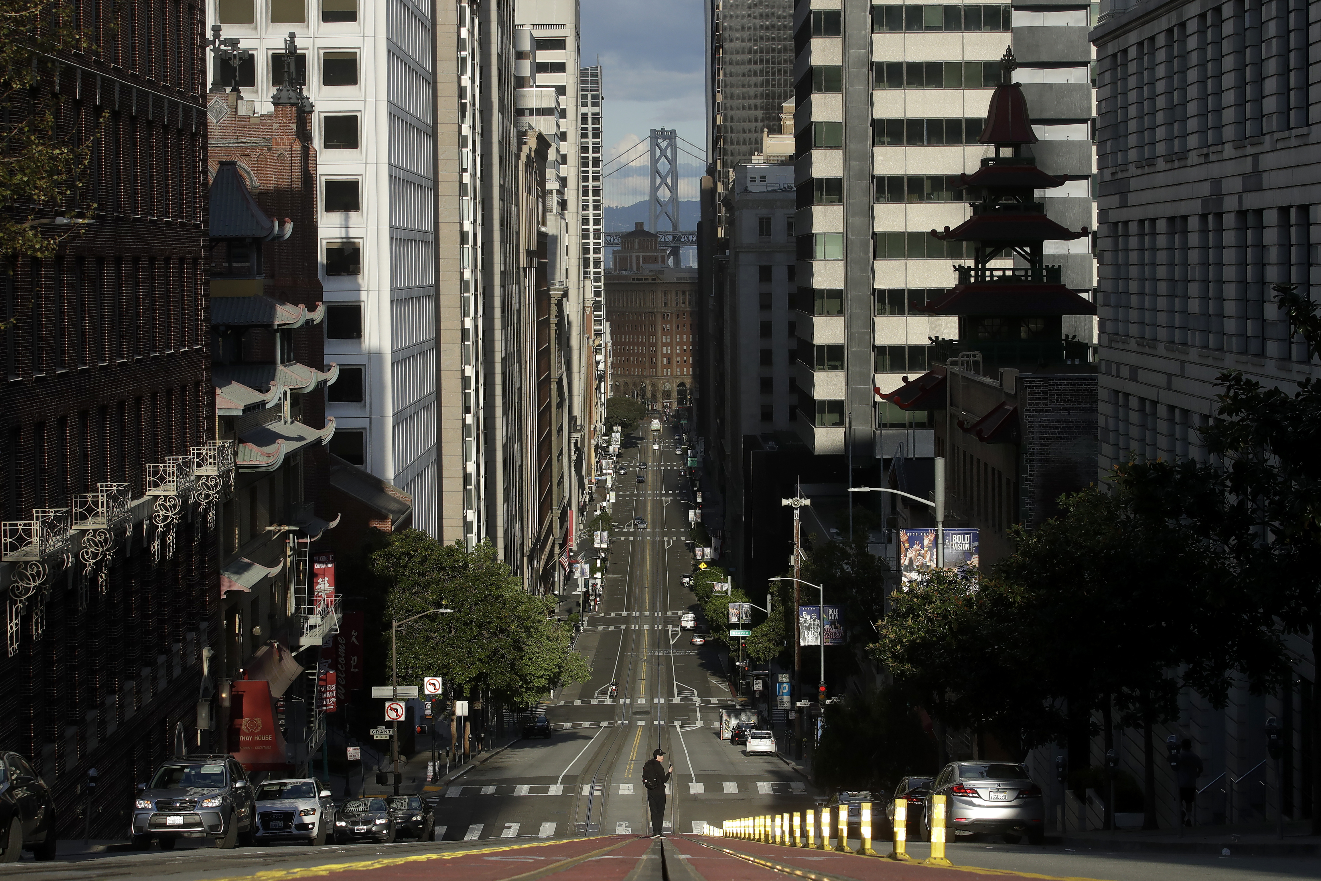 A man stands in the middle of a cable car tracks on a near empty street.
