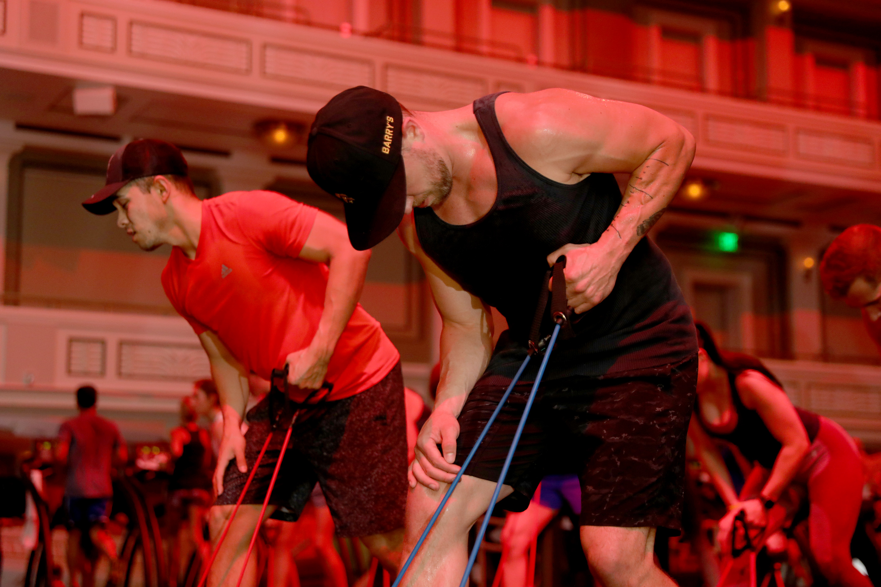 Men in a Barry's Bootcamp exercise class pull on elastic cords, June 2018, Nashville, Tennessee.