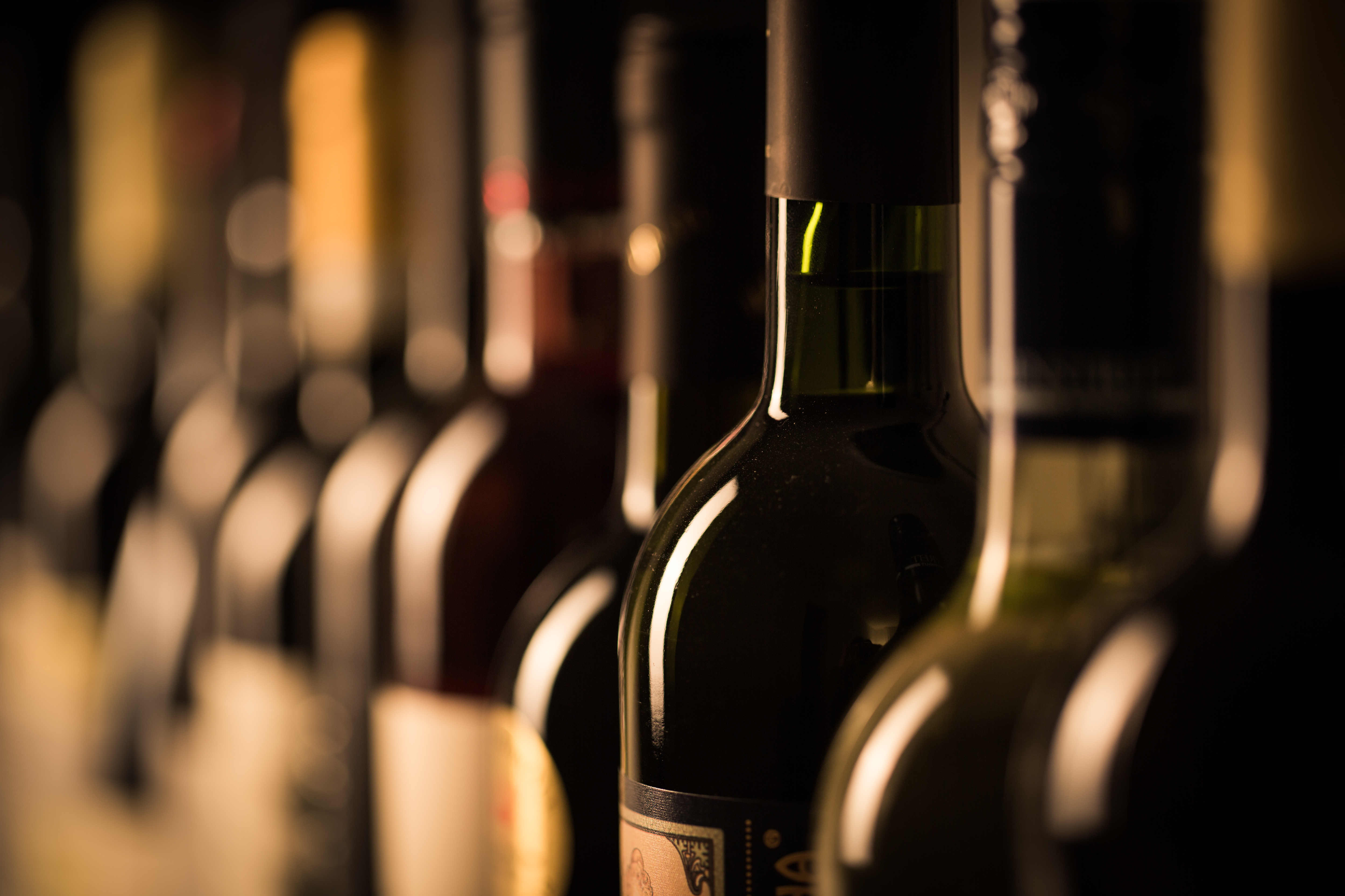 A closeup of a row of wine bottles