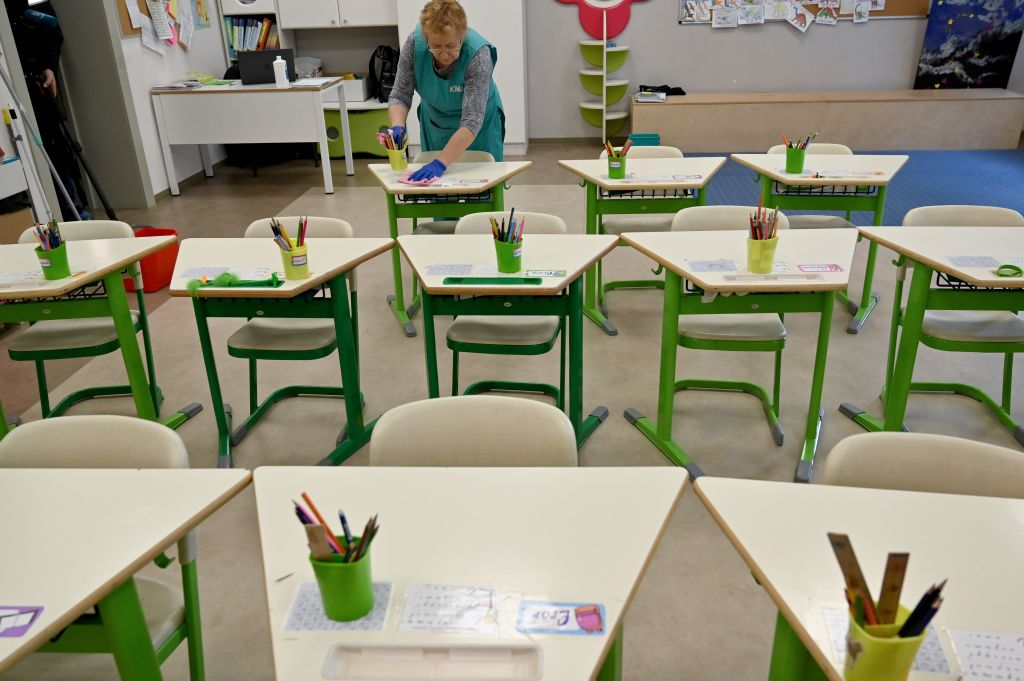 An employee disinfects a classroom of a school in the Ukrainian capital of Kiev on March 12, 2020. - Ukrainian authorities announced on March 11 they were closing schools and universities across the country for three weeks to prevent the spread of the novel coronavirus.