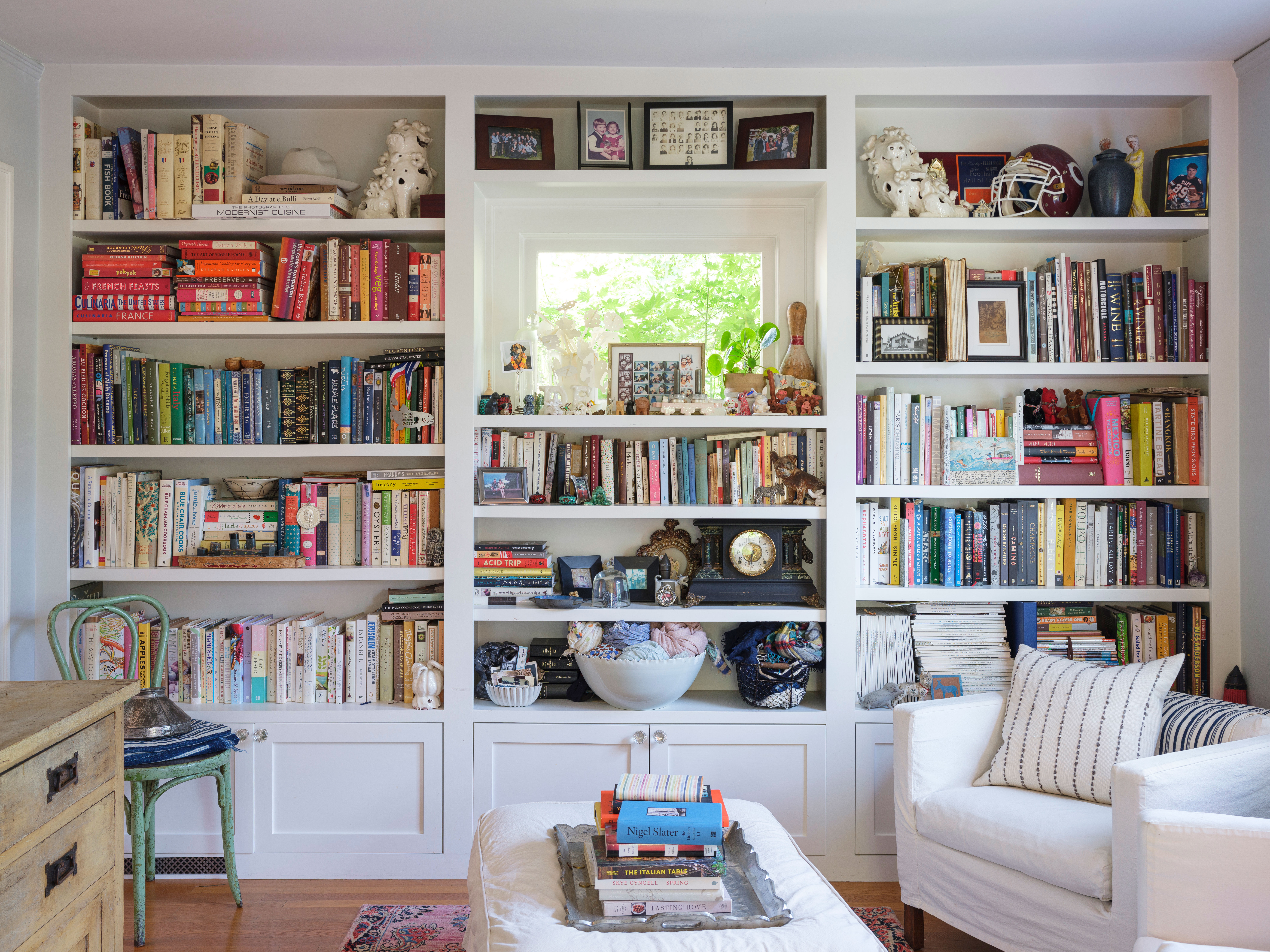 A living area with a white couch, table, chair, and desk. There are white built-in shelves on the wall. There are books, various objects, and works of art on the shelves.
