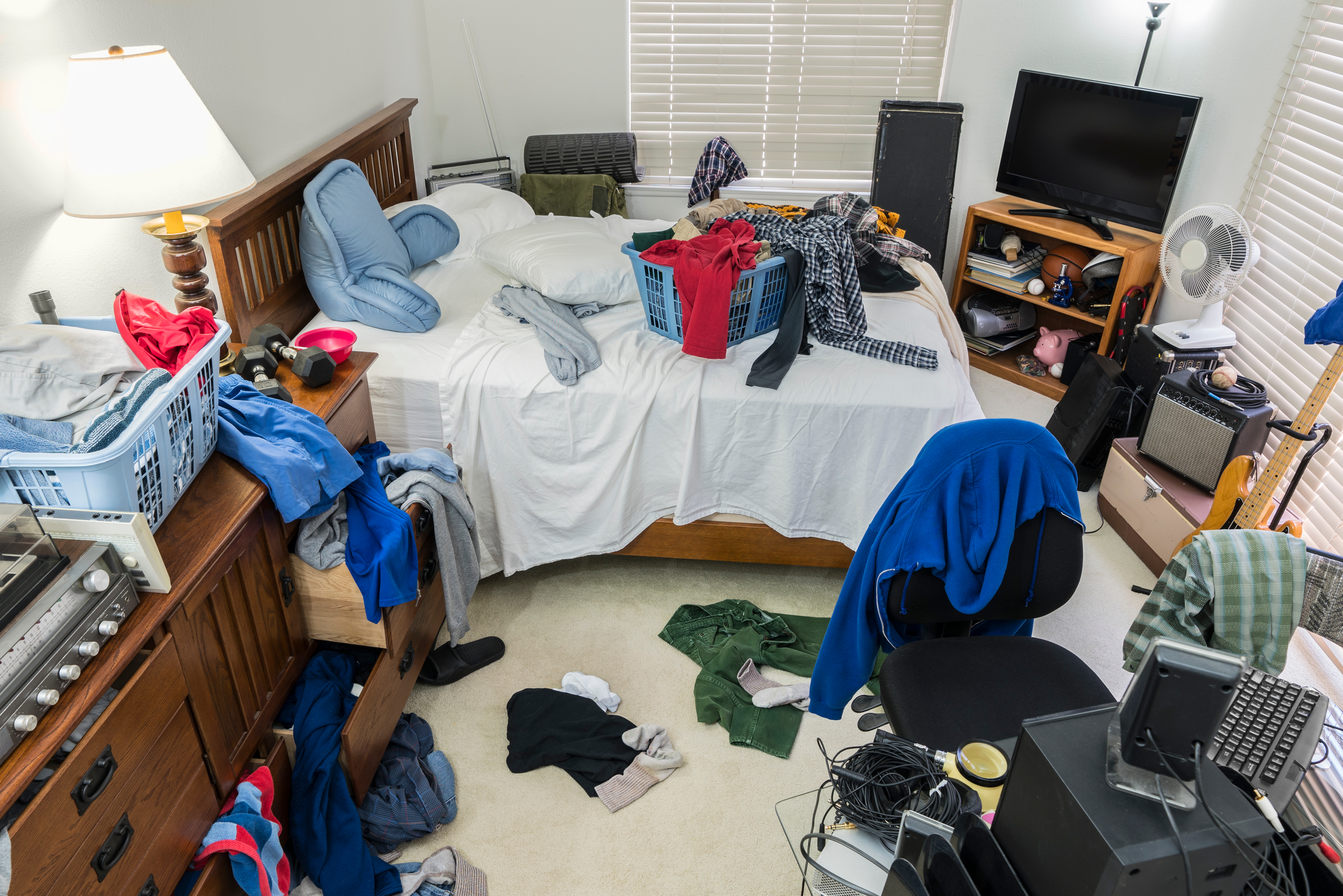 A very messy bedroom with clothes strewn about the furniture.