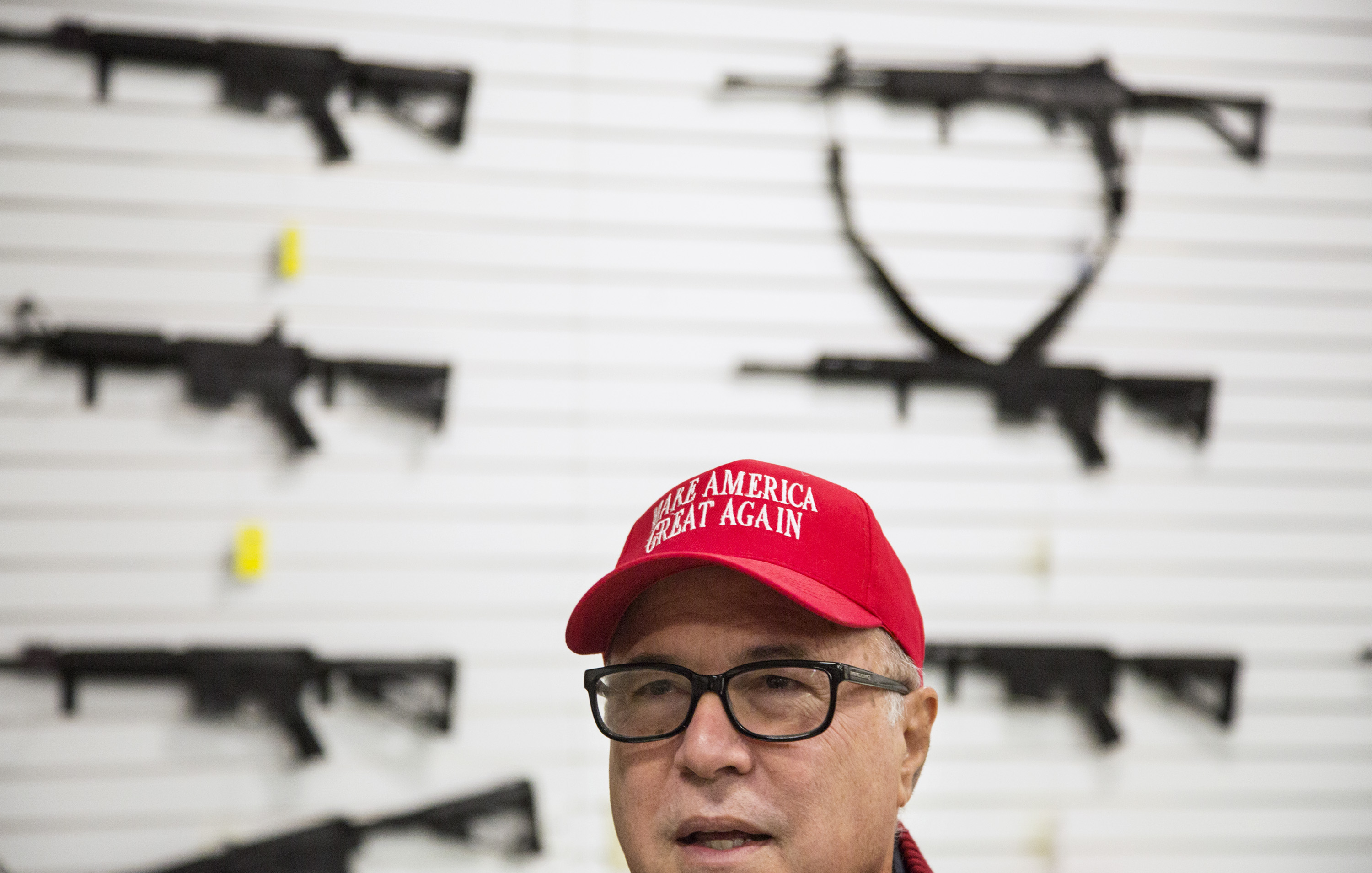A man in a MAGA hat in front of a gun shop display wall.