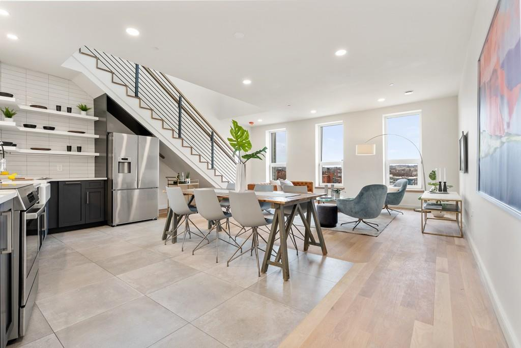 A capacious and open living room with a staircase into it and furniture.