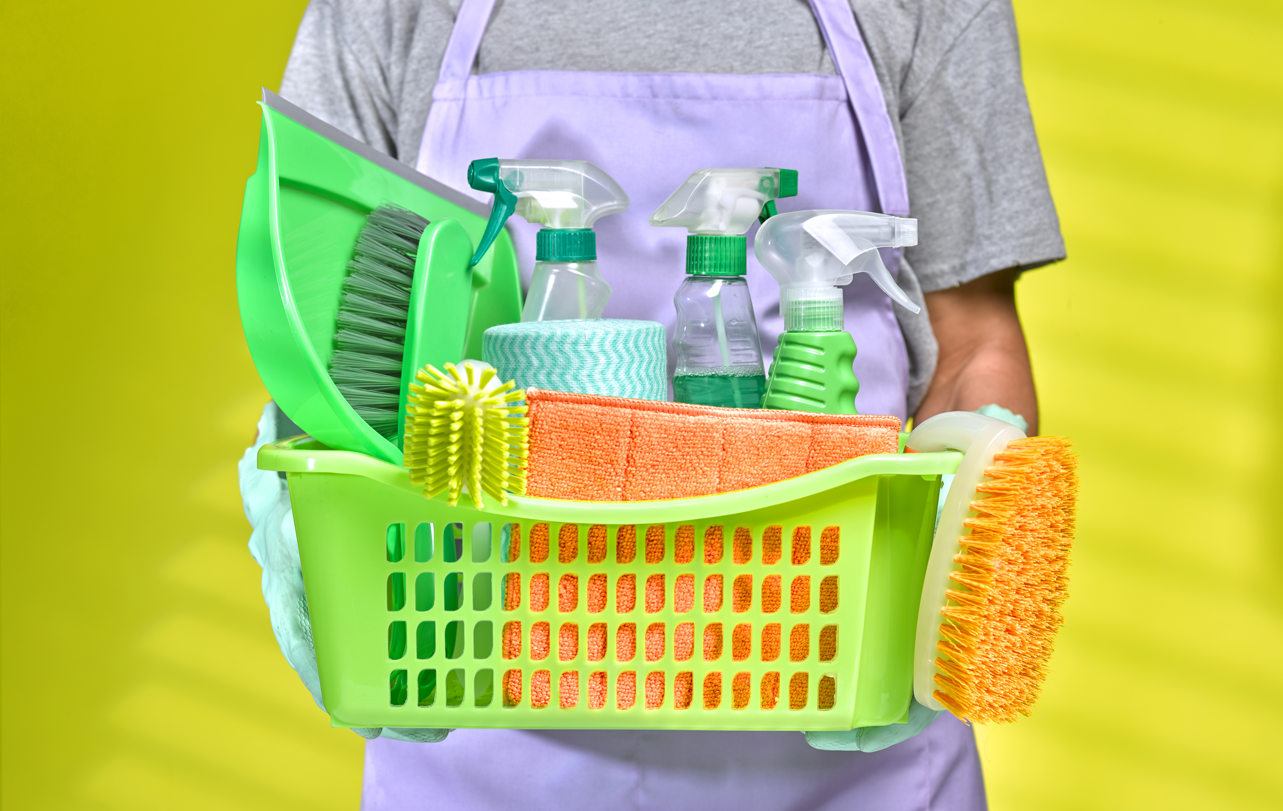 A person carrying a basket of cleaning products.