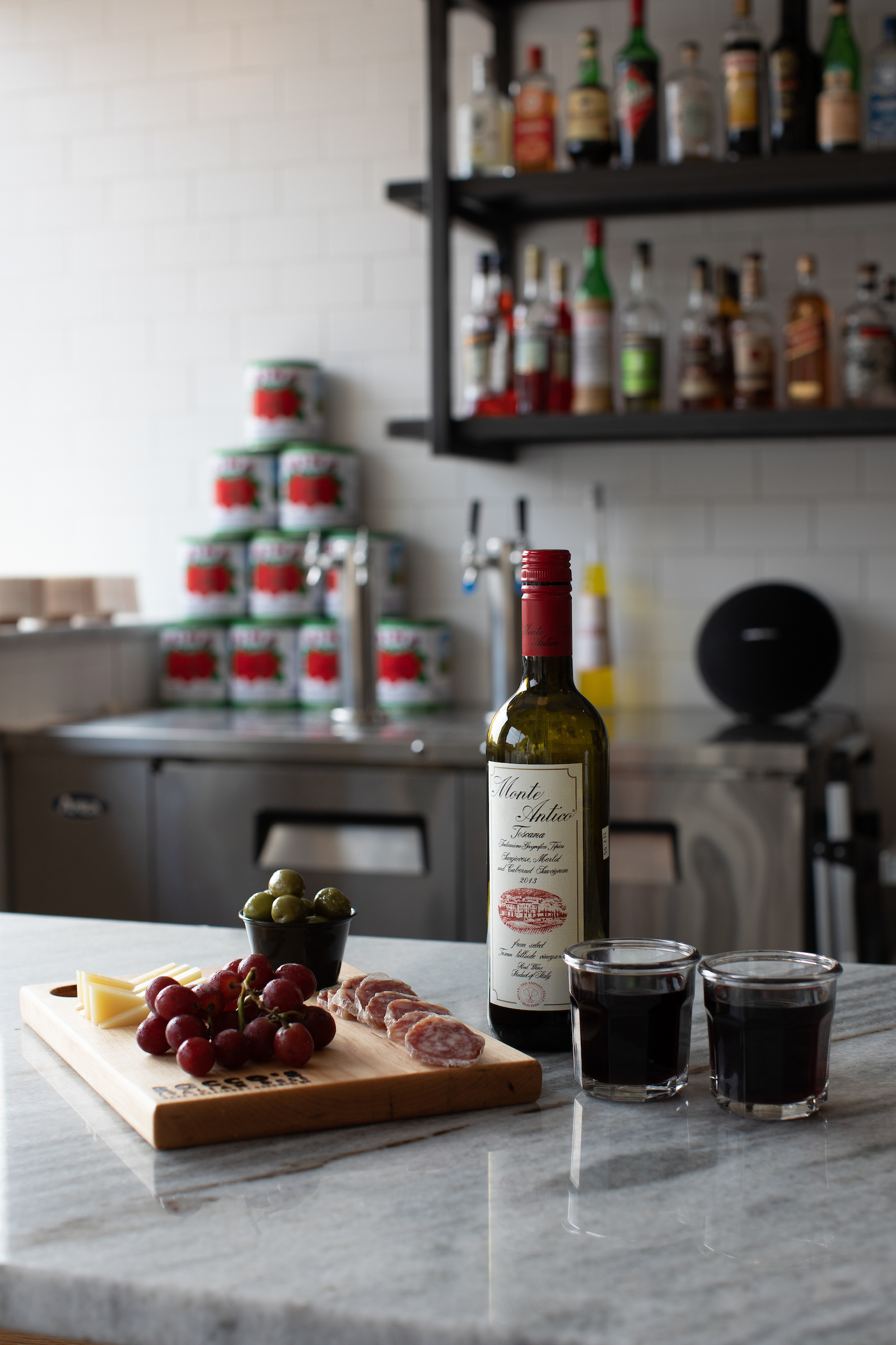 A bottle of wine, a charcuterie board, and two tumbler glasses filled with red wine.