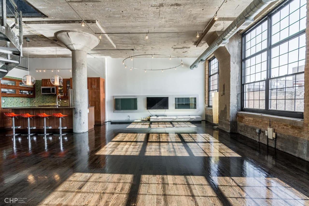 An image of a loft living room with tons of sunlight and a concrete ceiling.