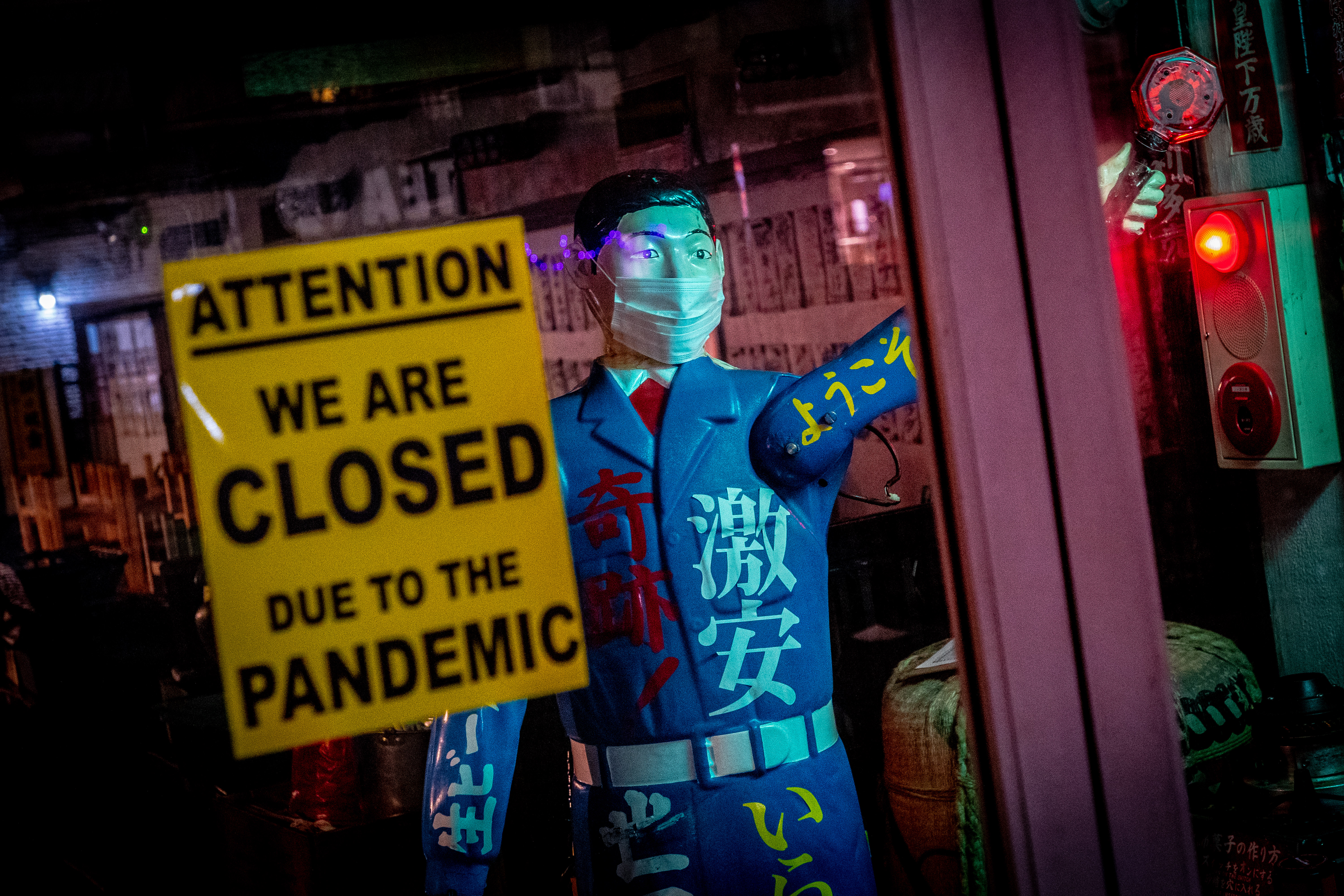 """A sign that says """"We are closed due to the pandemic"""" next to a statue wearing a face mask"""