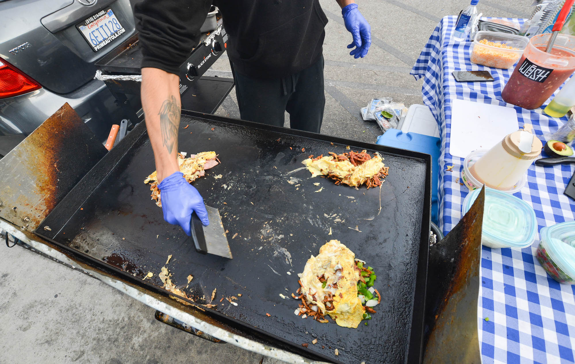 A hand with a blue glove prepares breakfast burritos from a street stand.