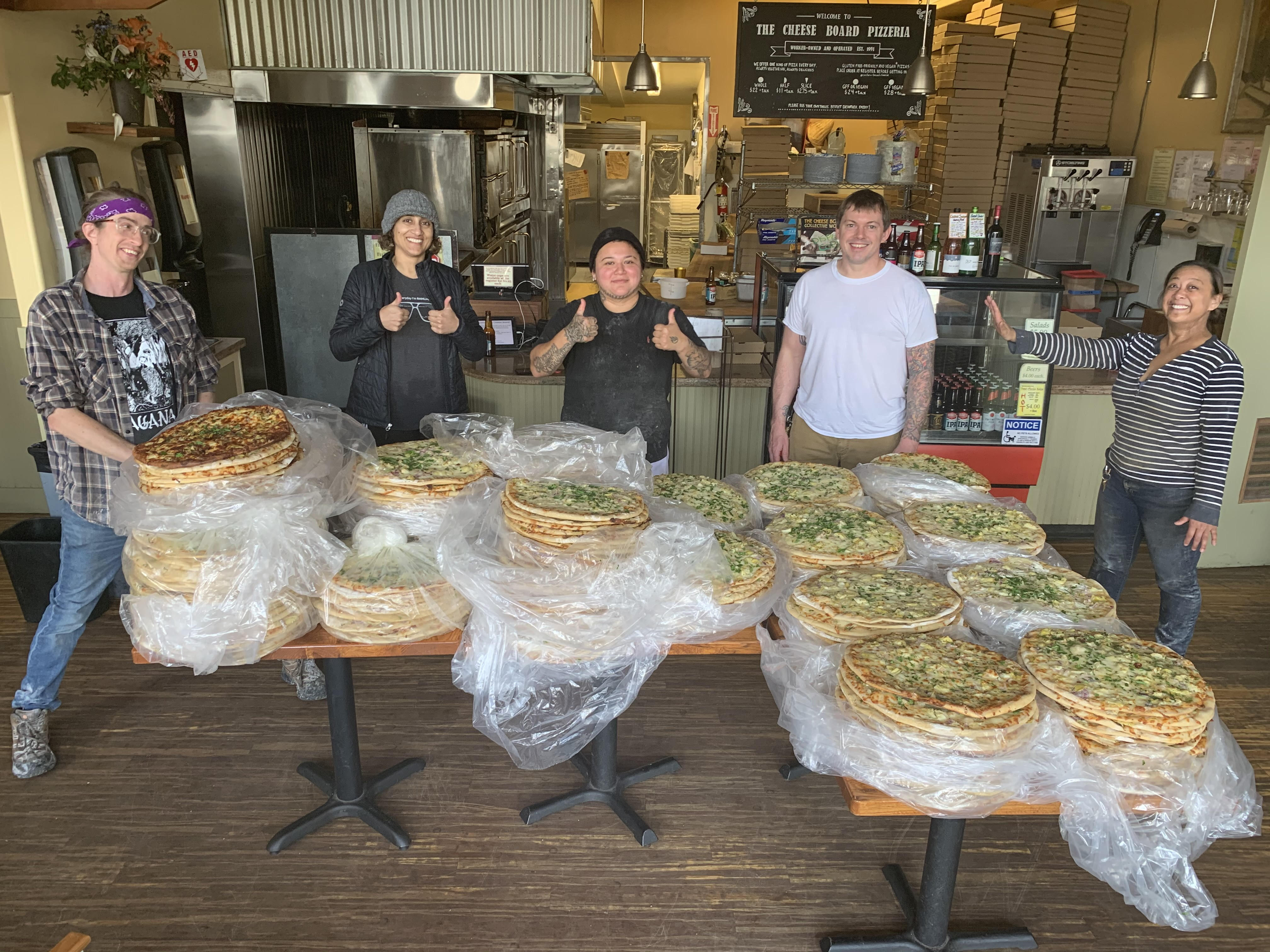 Members of the Cheese Board collective pose with pizzas they made to distribute to local shelters before closing down