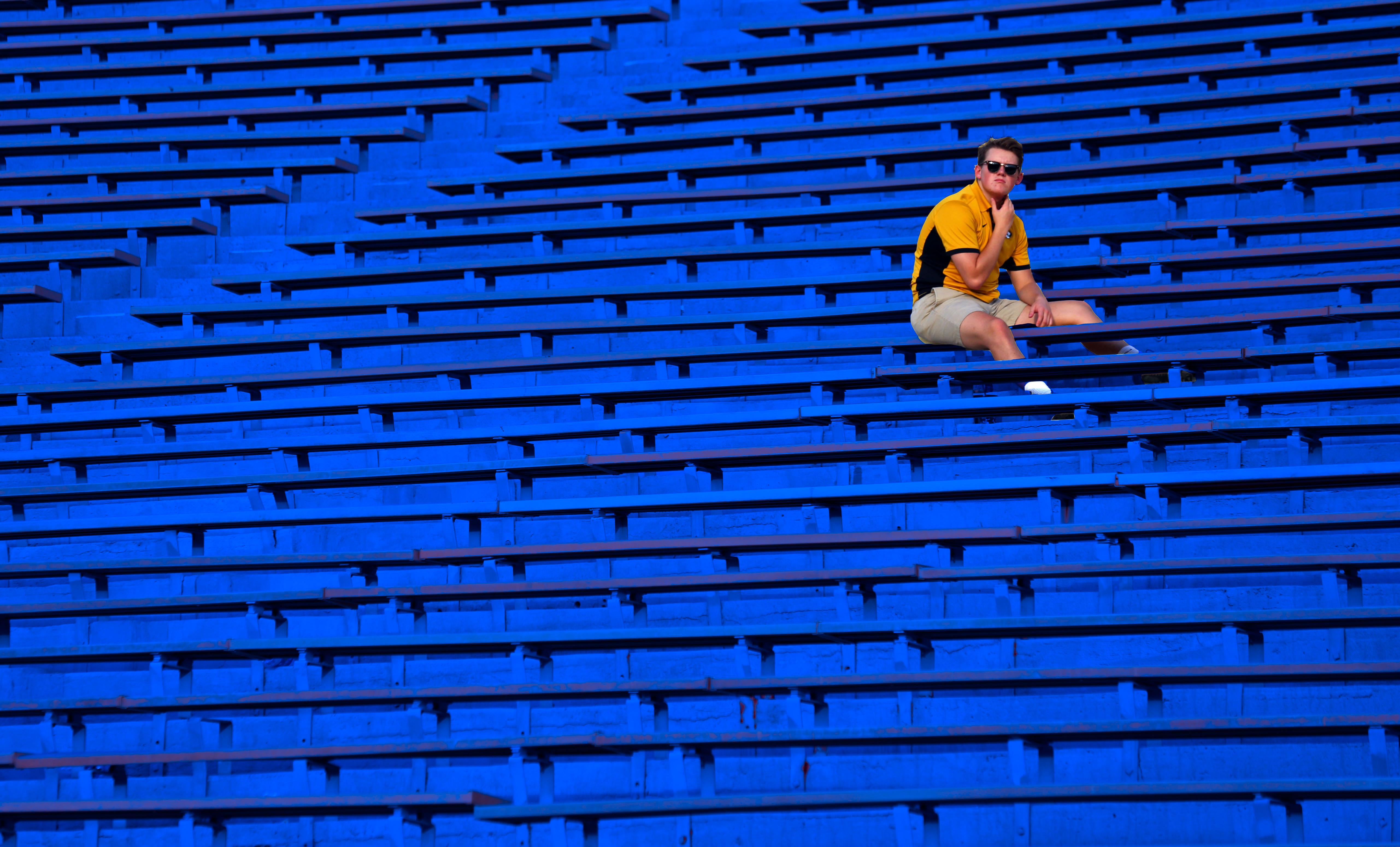 A fan sitting in the bleachers alone.