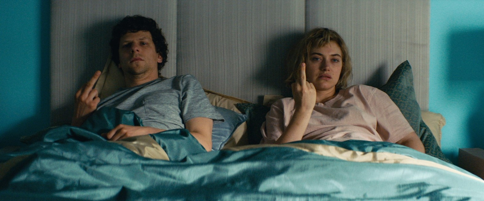 A young couple sit in bed, both flipping the bird.