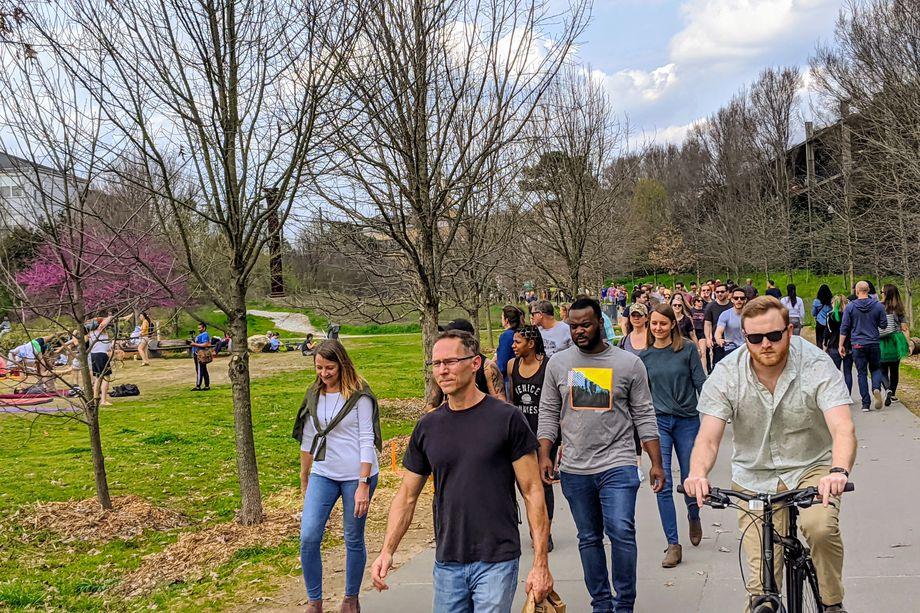 A photo of many people walking along a path near a bunch of trees in spring.