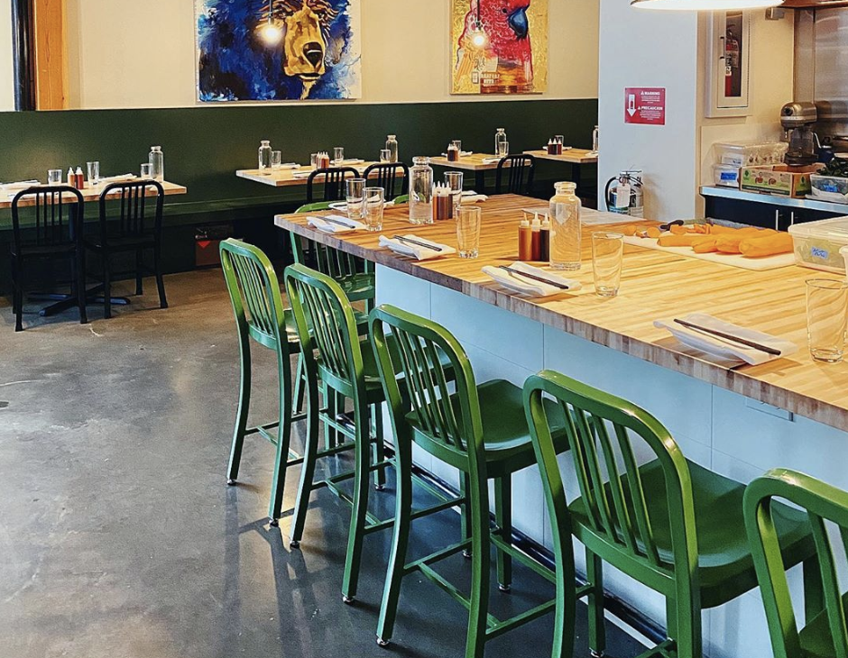The interior of Revel's Fremont location, with green chairs and colorful paintings in the background.