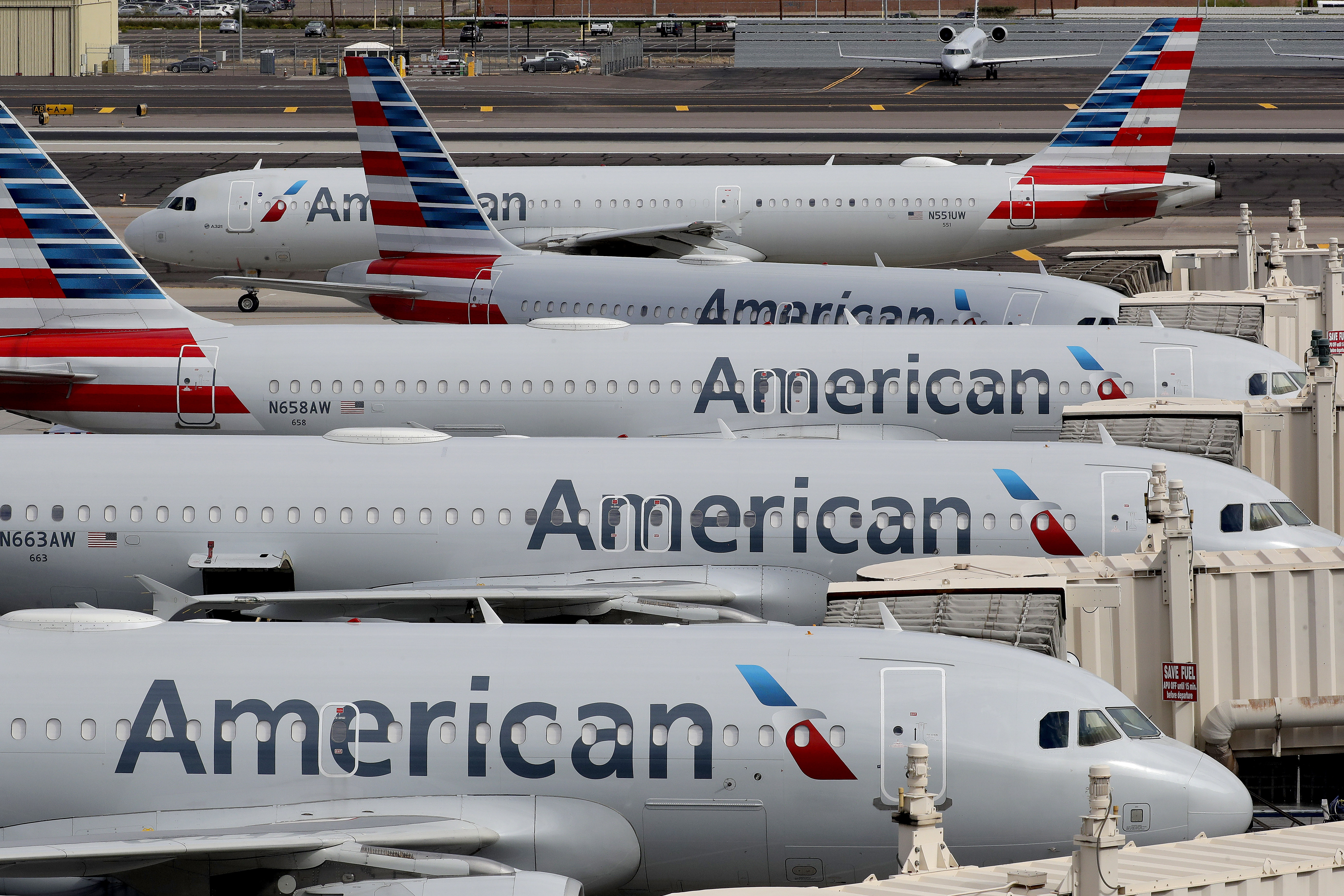 In this Wednesday, March 25, 2020 file photo, American Airlines jets sit idly at their gates as a jet arrives at Sky Harbor International Airport in Phoenix.